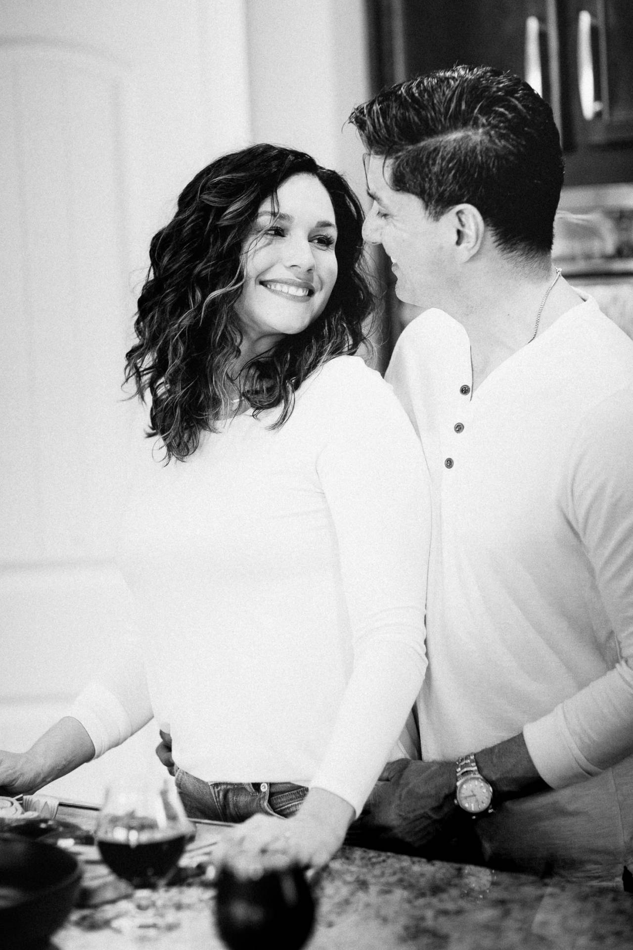 Black and white photo of couple sharing a moment as they cook together in their home.