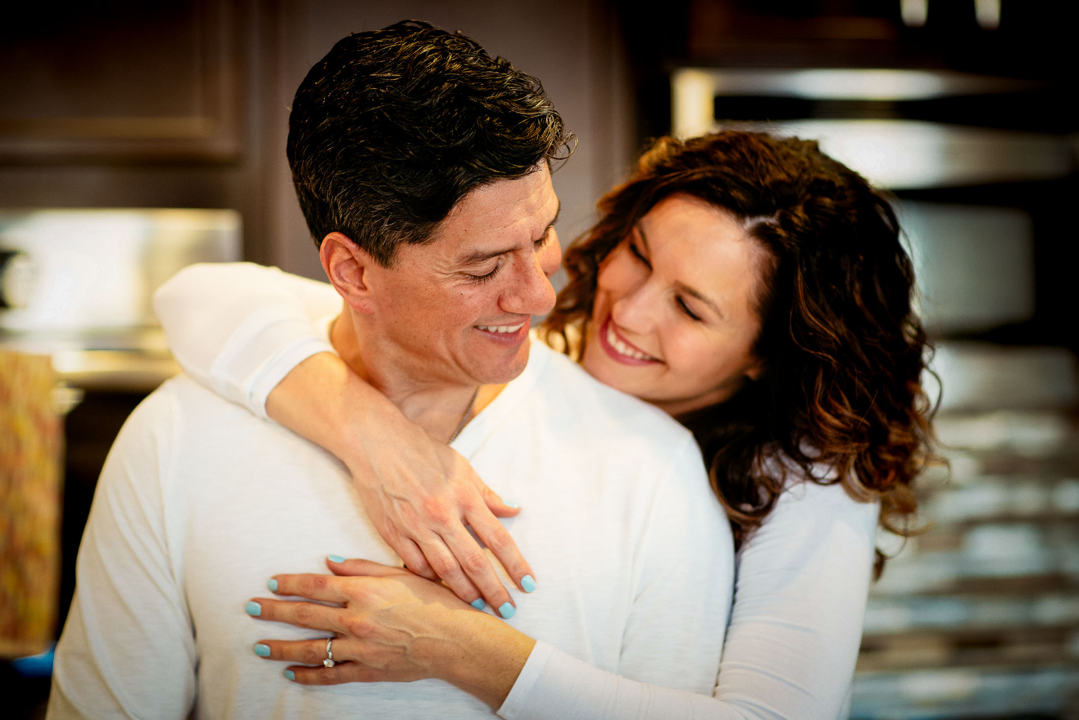 Couple embraces while cooking in their home.