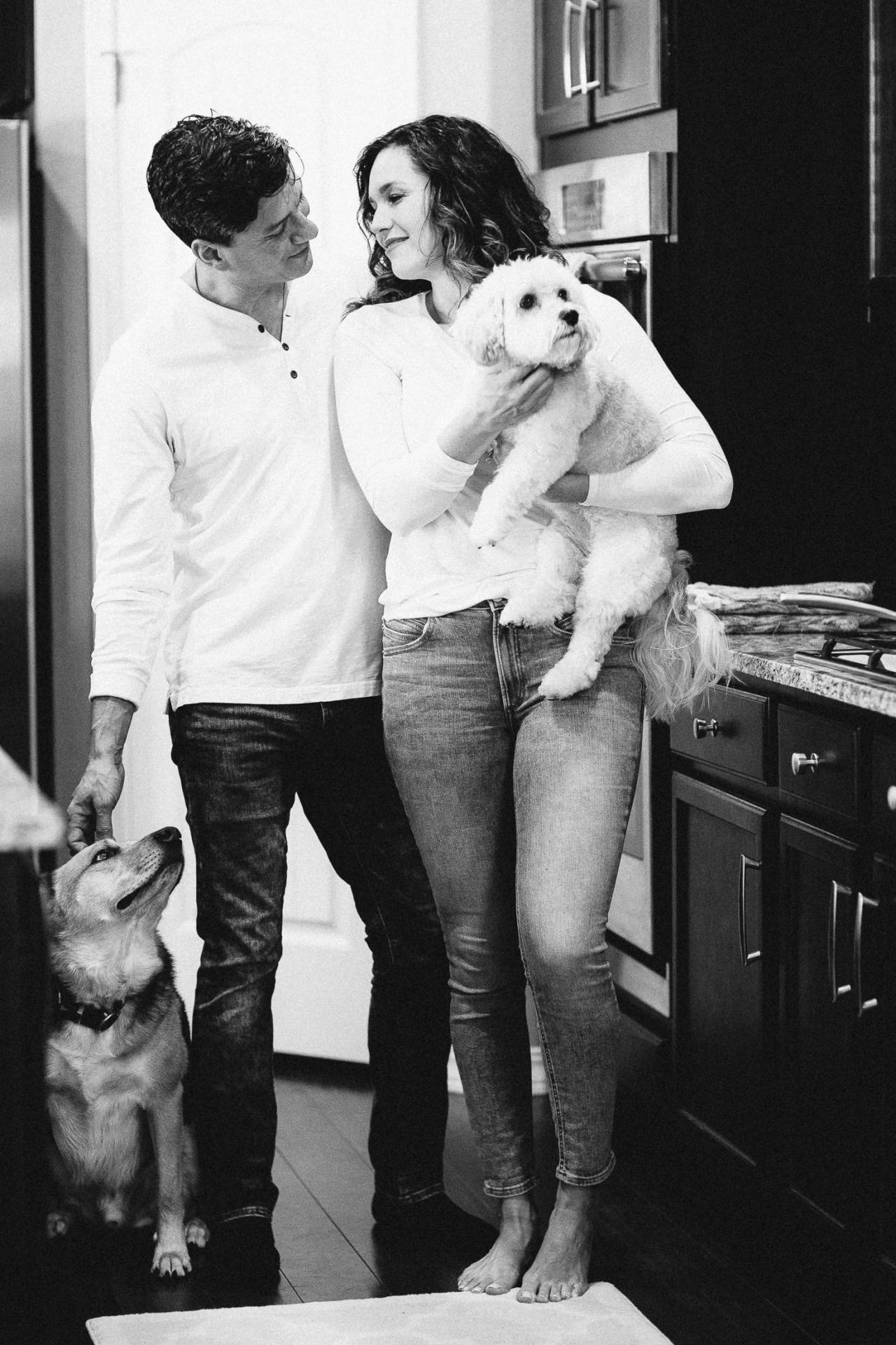 Black and white photo of coupel in the kitchen with their two dogs.