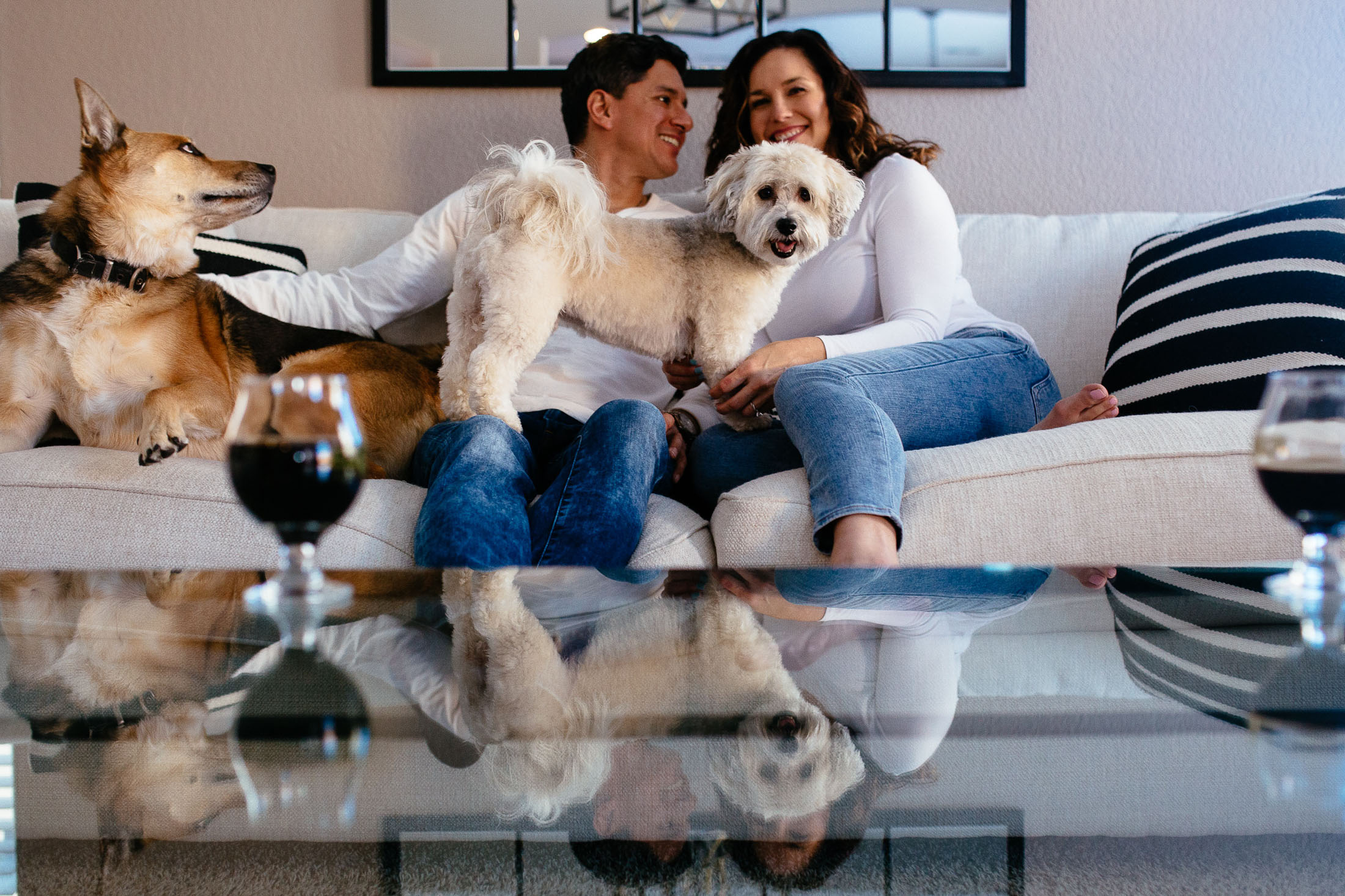 Couple sits on their couch with their dogs.