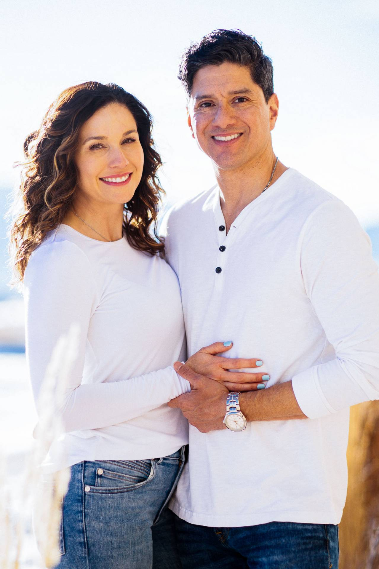 Couple in white shirts holds each other outside their home.