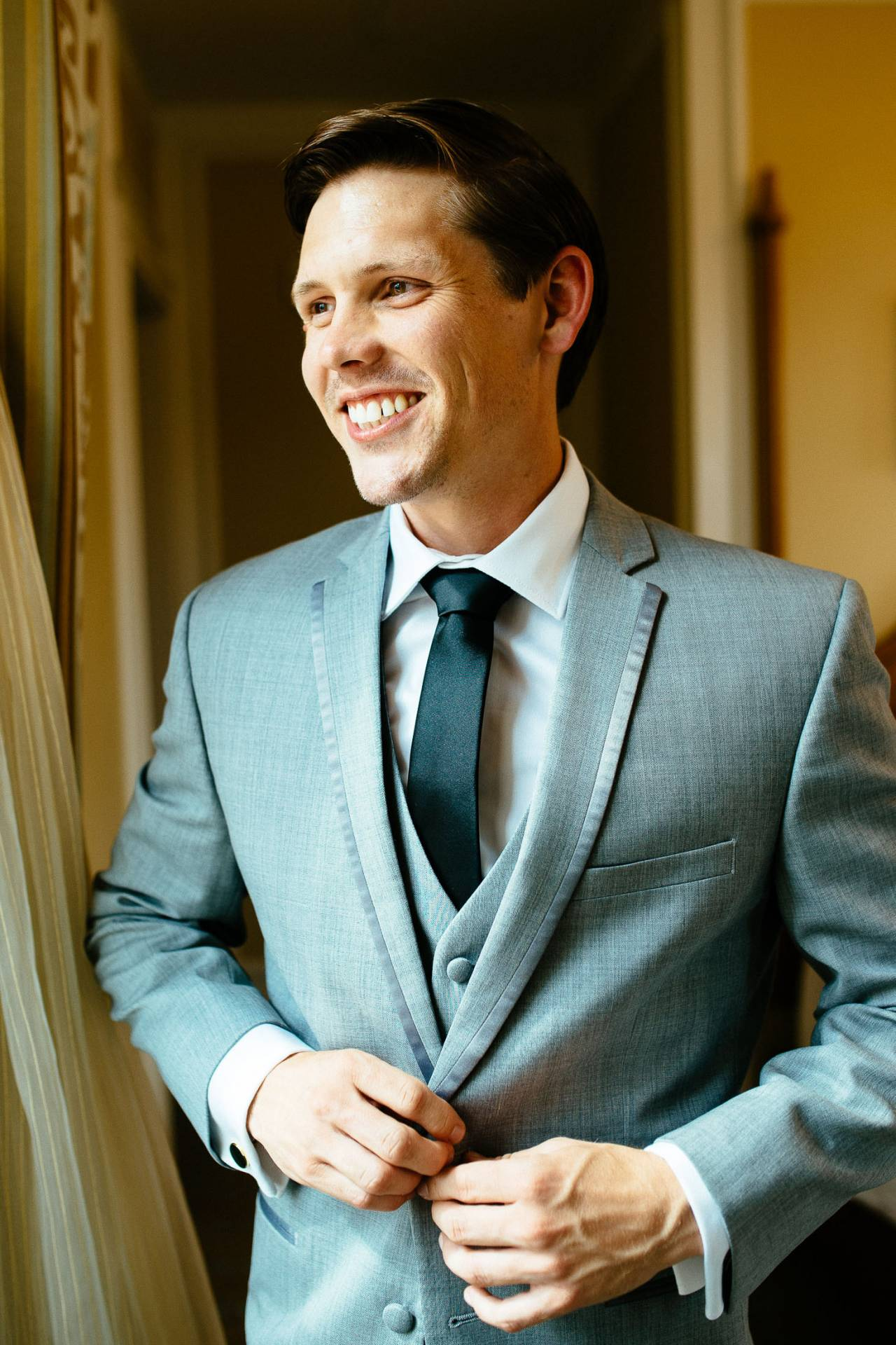 Groom in gray suit buttons his coat and smile on his wedding day.