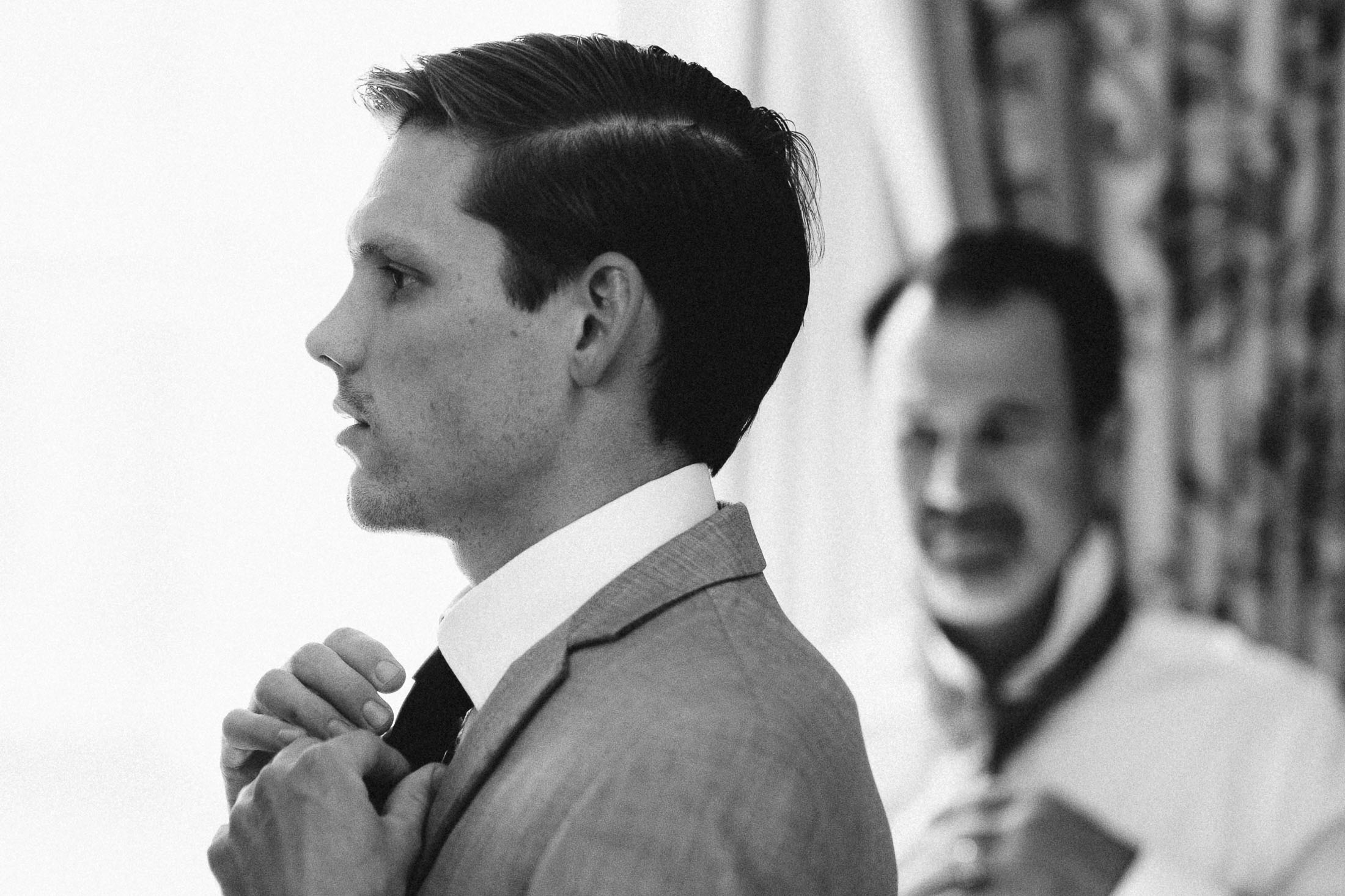 Black and white photo of groom fixing his tie inside a hotel room at The Broadmoor.