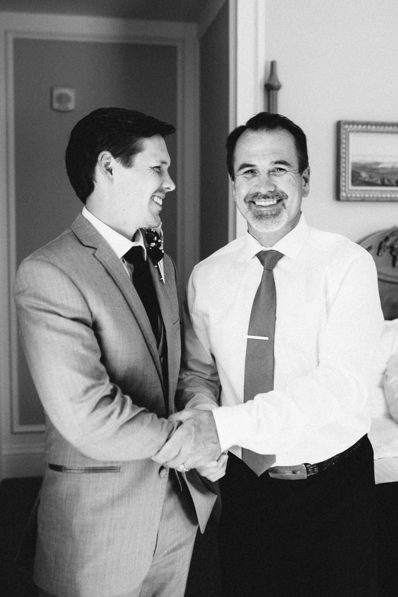 Black and white photo of groom shaking hands and smiling with his father on his wedding day at The Broadmoor.