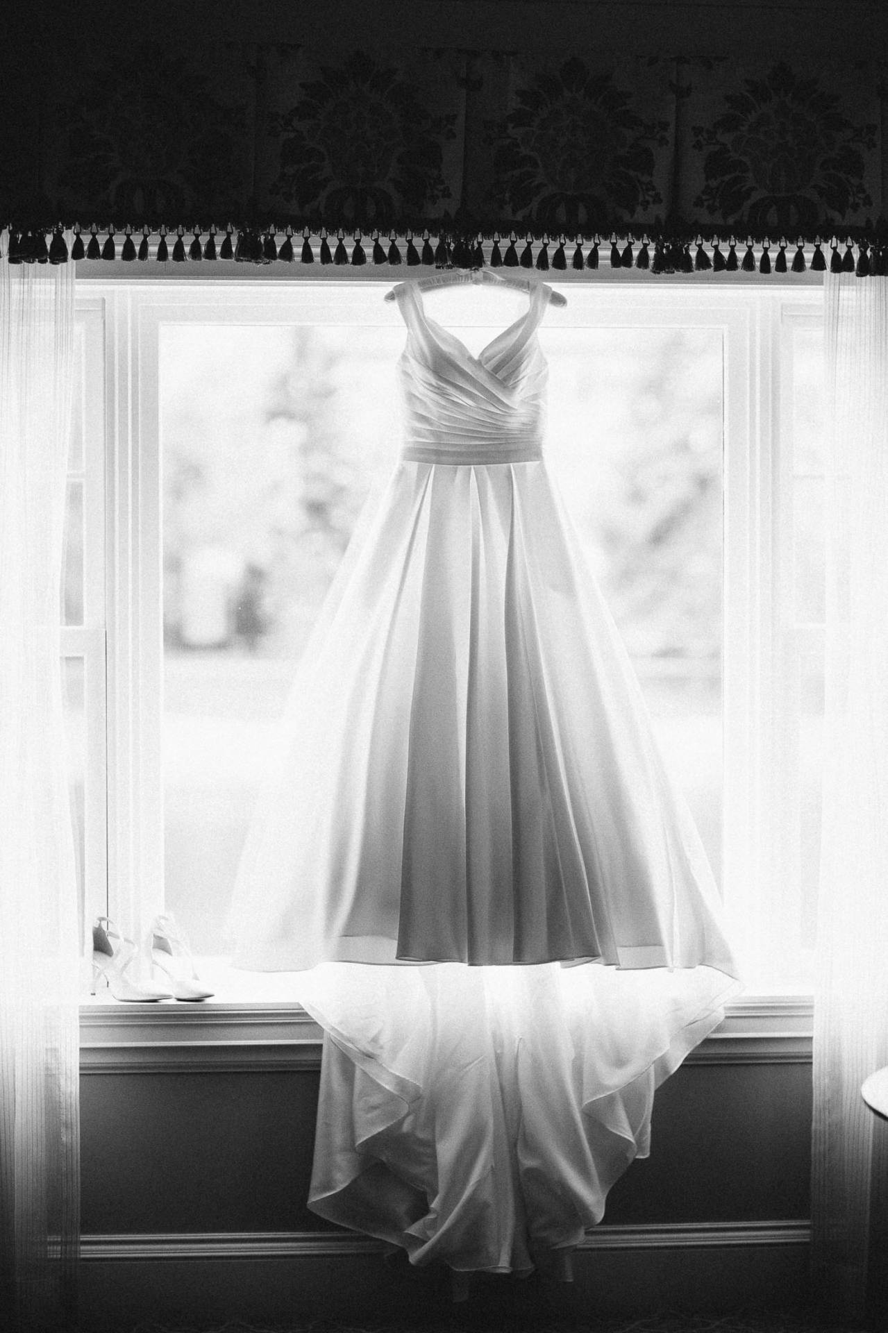 Black and white photo of wedding dress hanging in hotel room suite in front of a window at The Broadmoor.