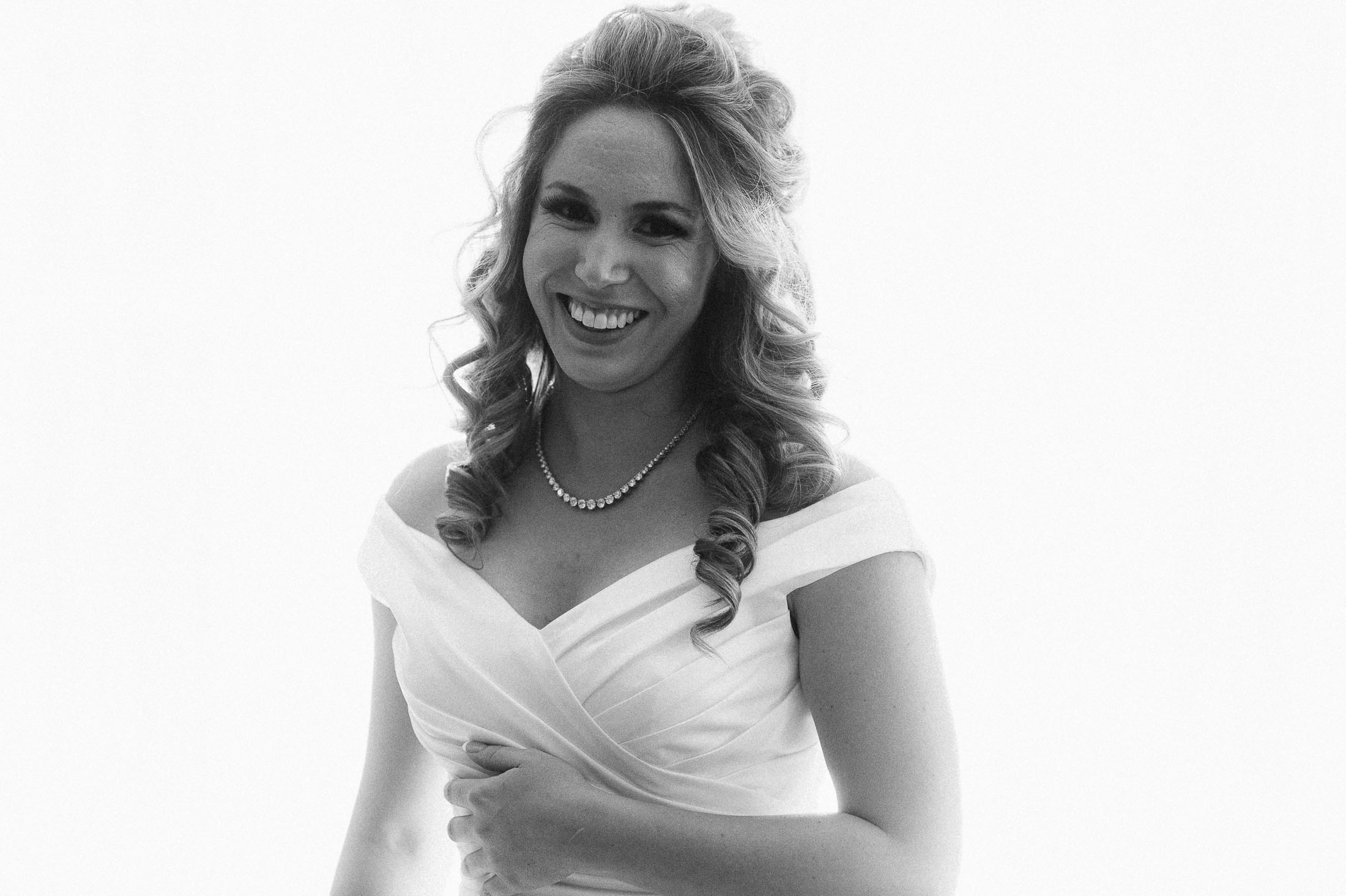Black and white photo of bride in wedding dress smiling.