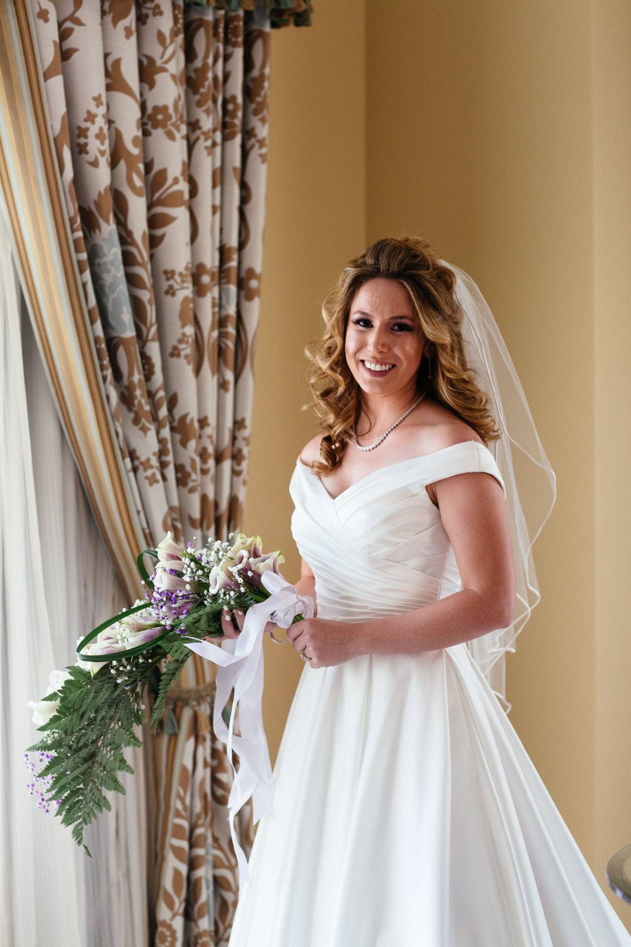 Portrait of bride in wedding dress holding cascading bouquet at The Broadmoor.