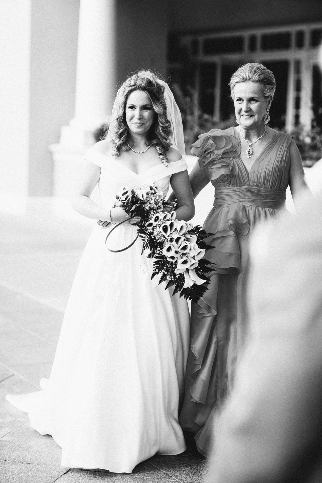 Black and white photo of bride walking down the aisle with her mother on her wedding day at The Broadmoor.
