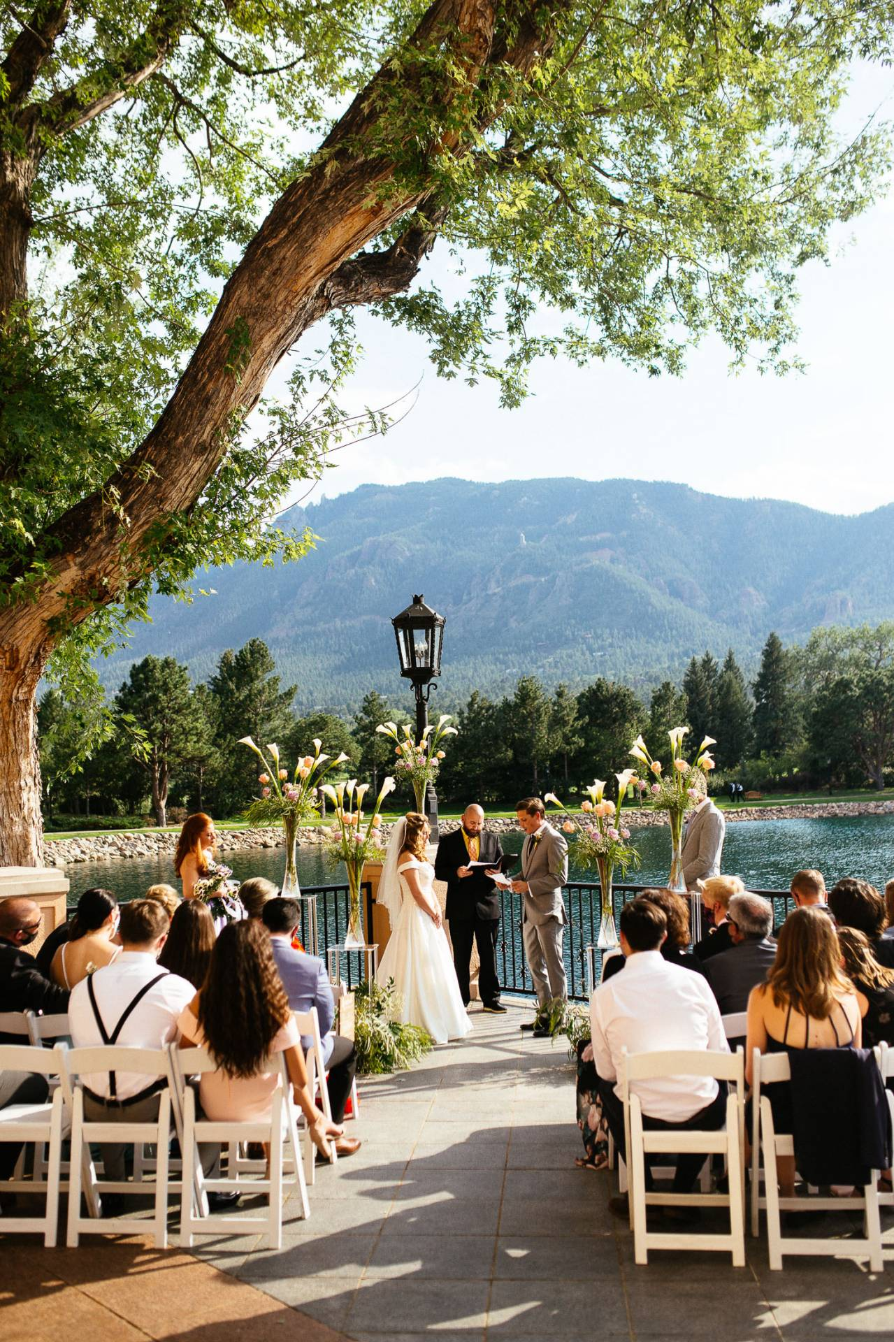 Wedding ceremony underneat oak tree with views of Cheyenne Mountain at The Broadmoor.