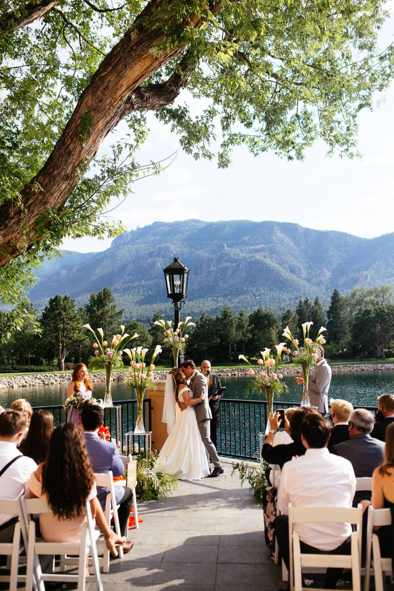 Bride and groom kiss at the end of the wedding ceremony at The Broadmoor's South Tower.