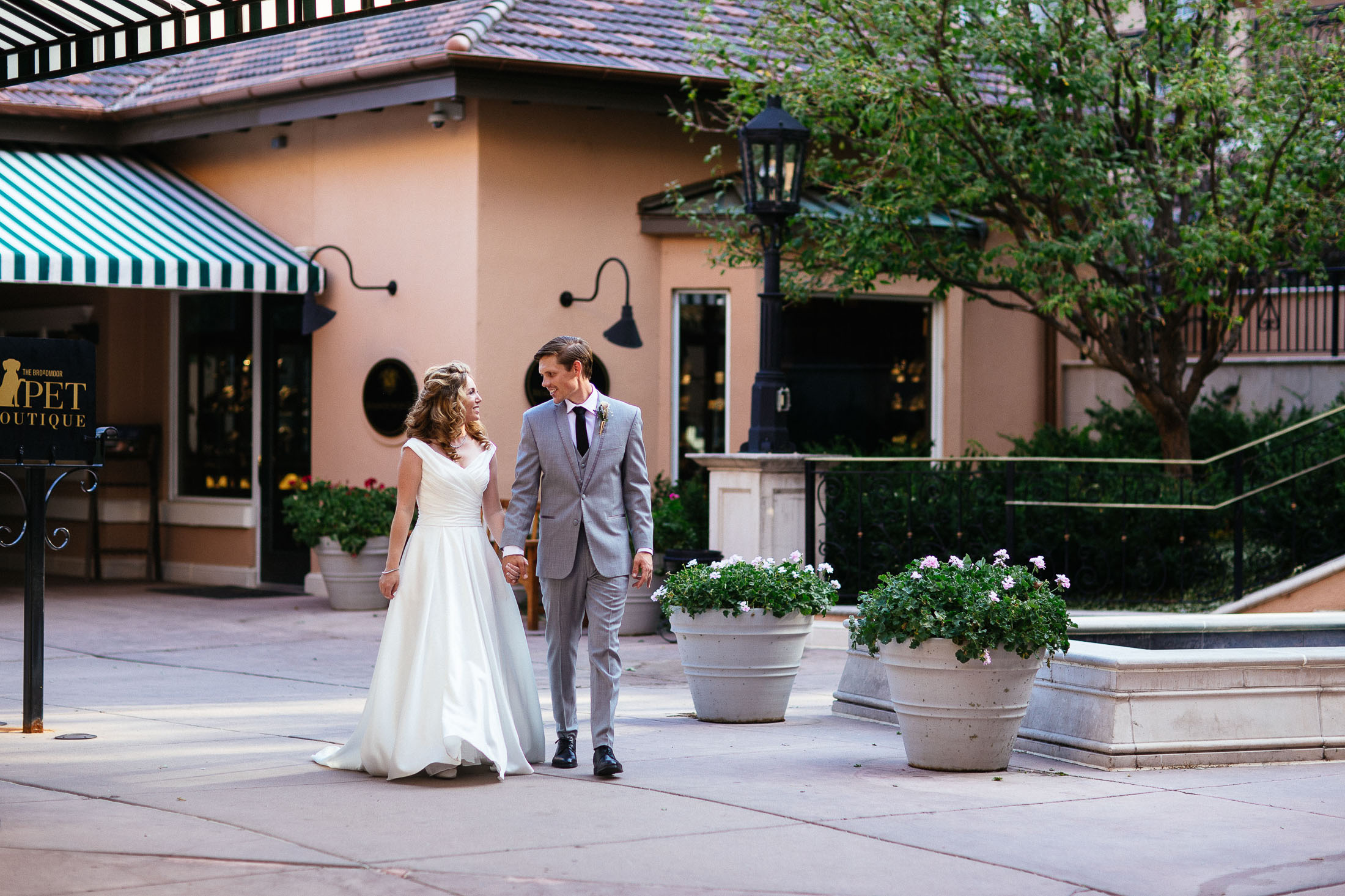 Bride and groom walk together through a shopping plaza at The Broadmoor.