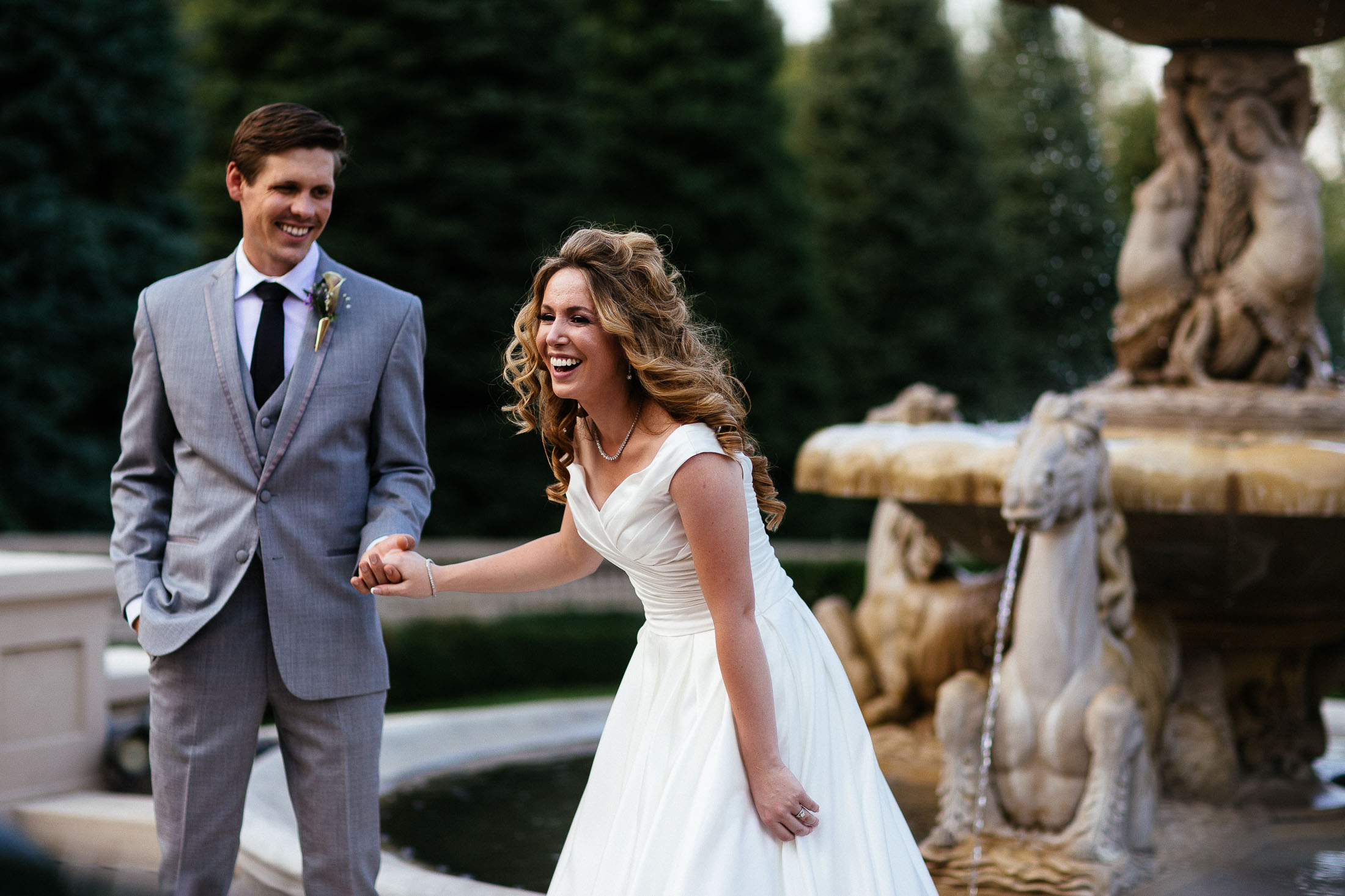Bride holds groom's hand and laughs on their wedding day at The Broadmoor.