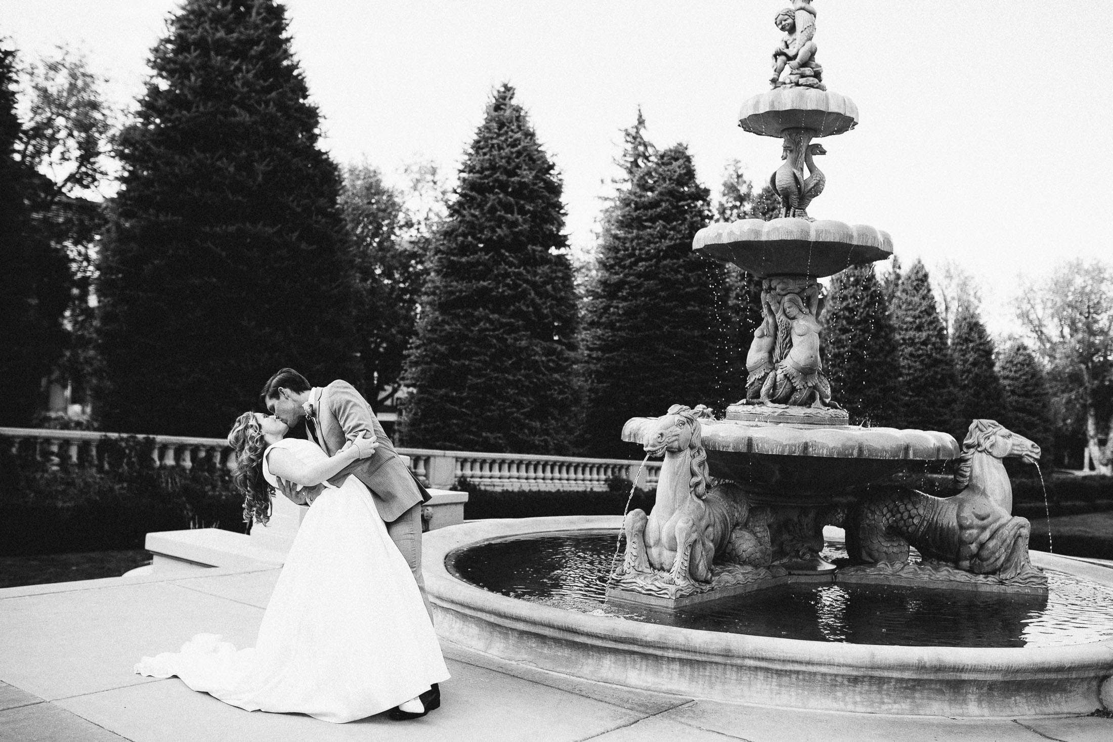 Black and white photo of bride and groom kissing in front of the fountain at The Broadmoor.