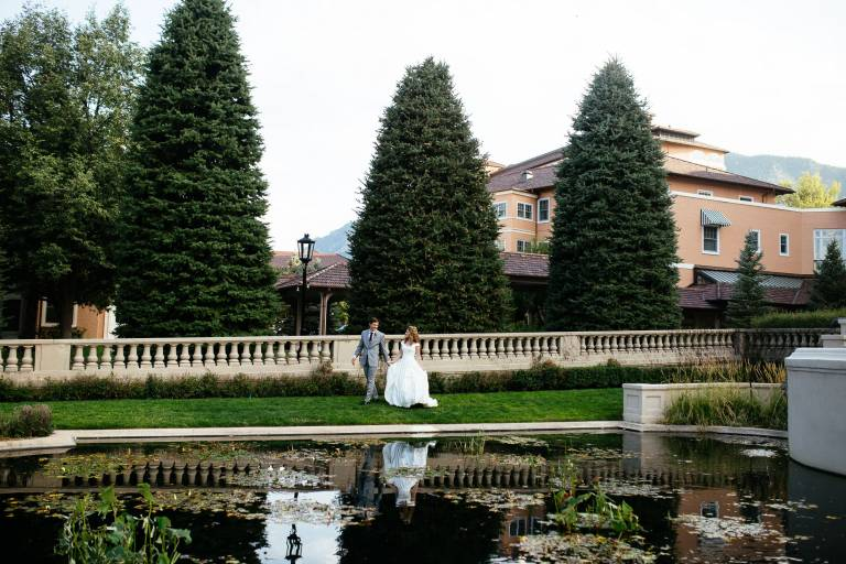 Bride and groom walk together by the koi pond at The Broadmoor.