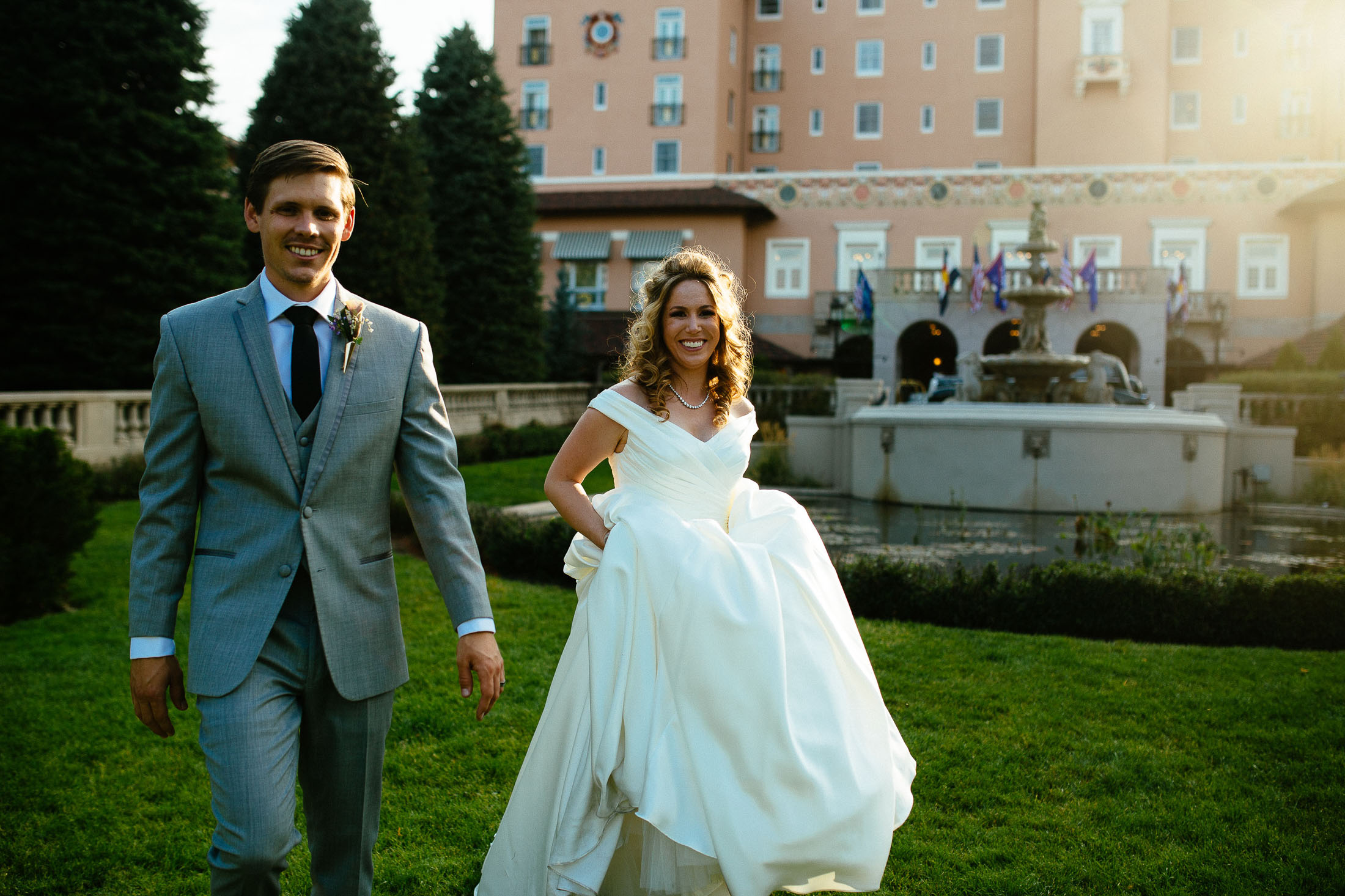 Bride and groom walk together as the sun sets behind the entrance to The Broadmoor.