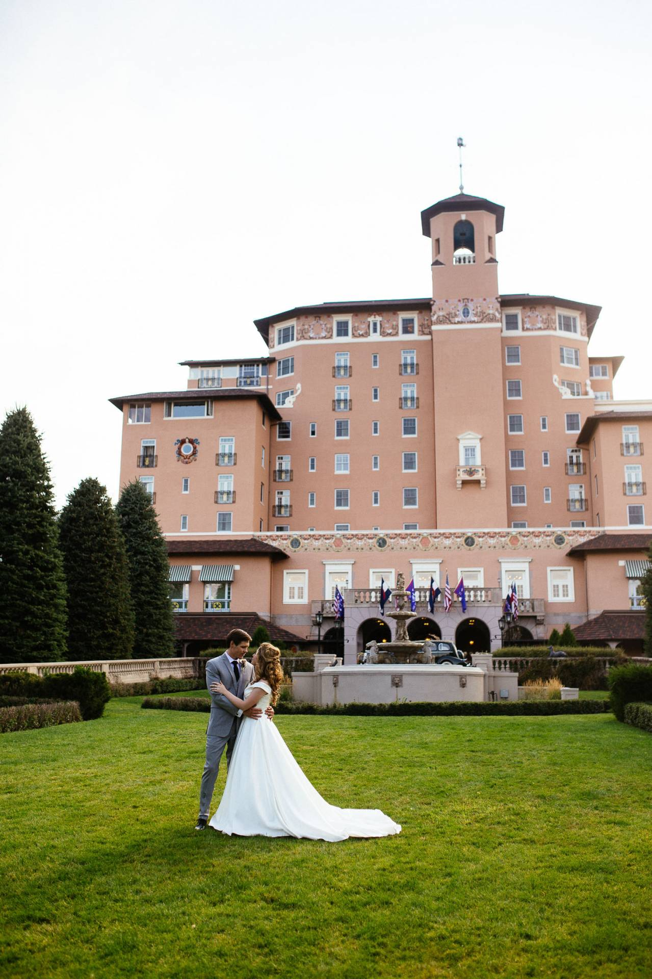 Wedding couple embrace and kiss in front of the entrance to The Broadmoor.