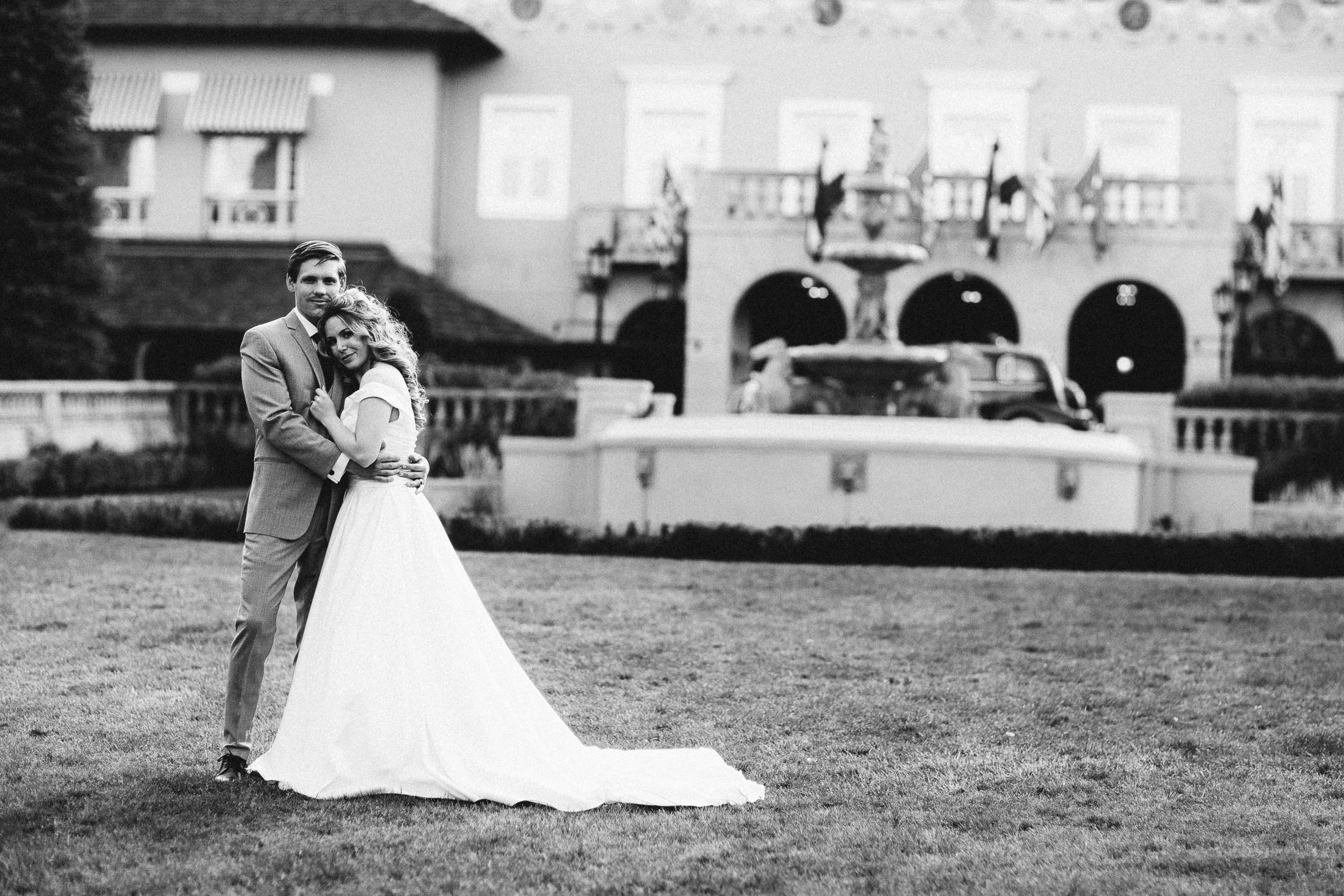 Black and white wedding photo of bride and groom embracing in front of the entrance to The Broadmoor.