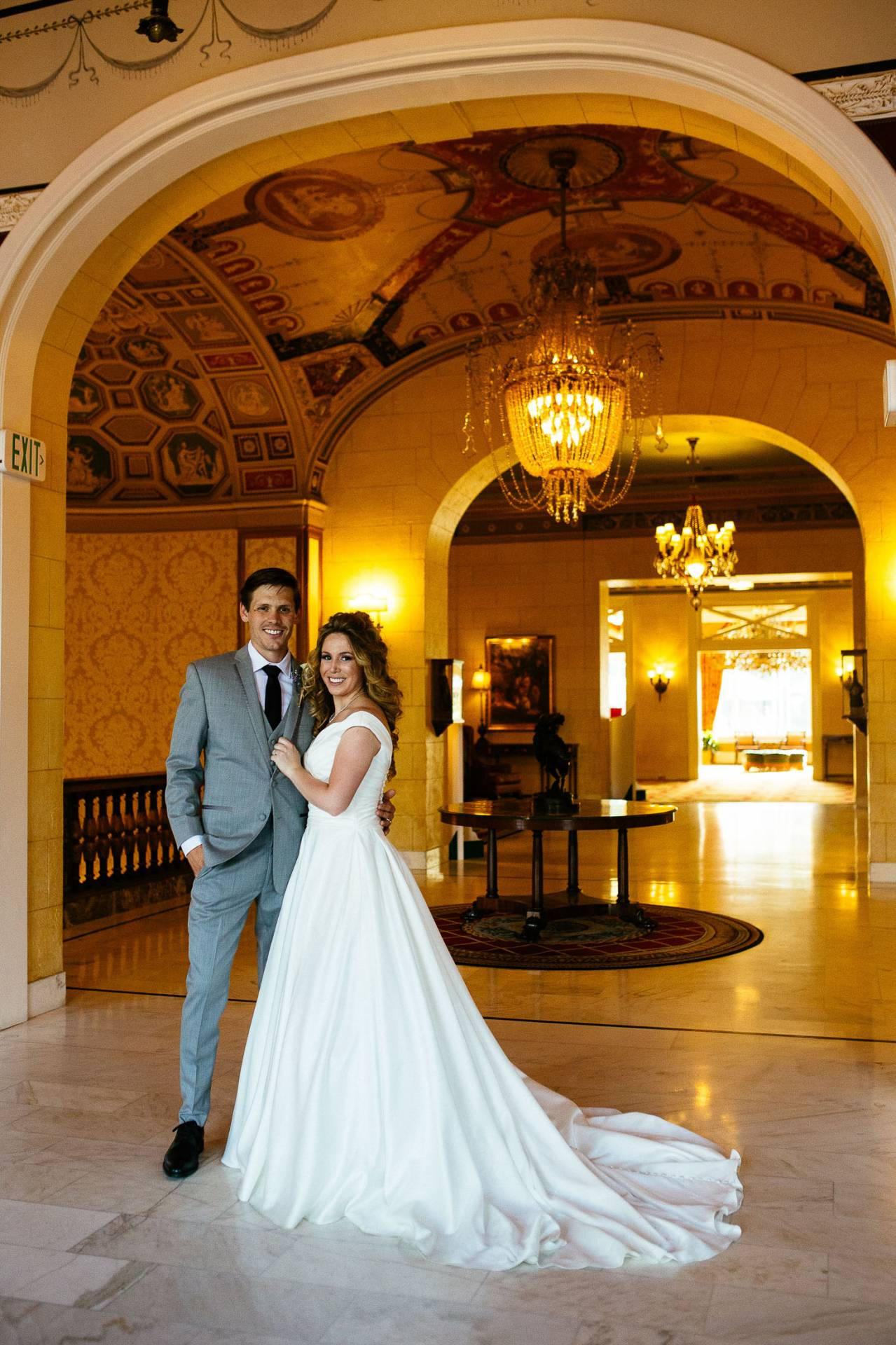 Bride and groom inside the main entrance to The Broadmoor with chandelier in the background.