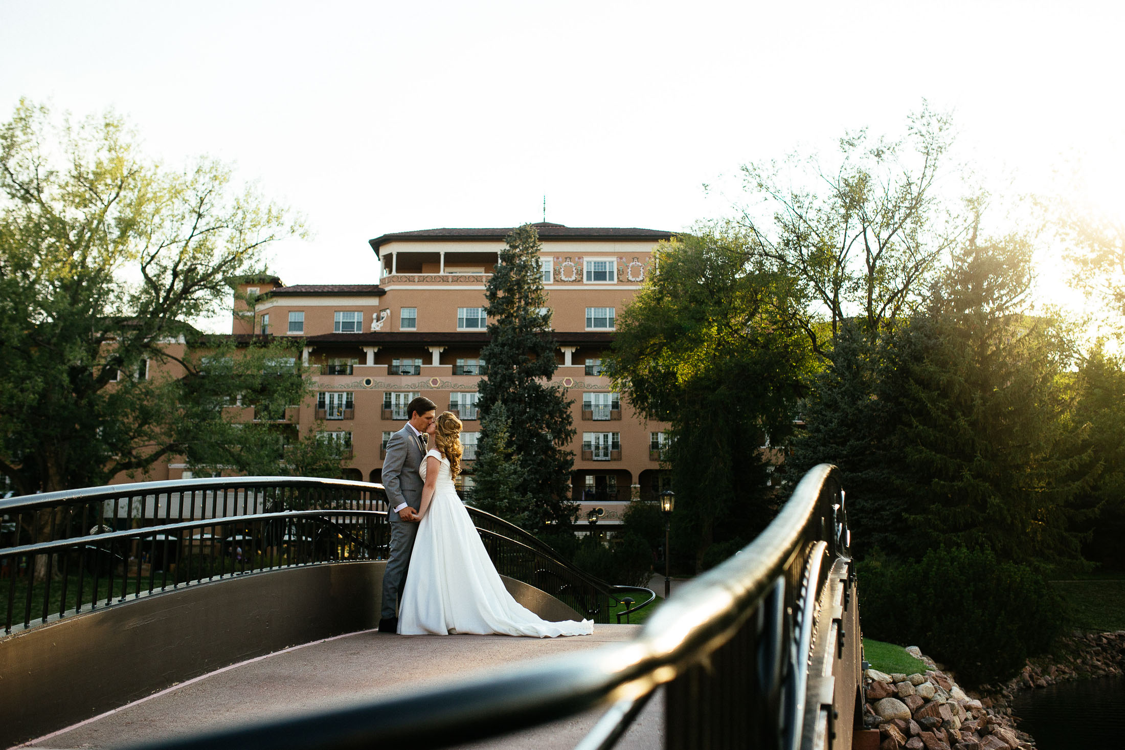 Bride and groom kiss on the bride over the lake at The Broadmoor.