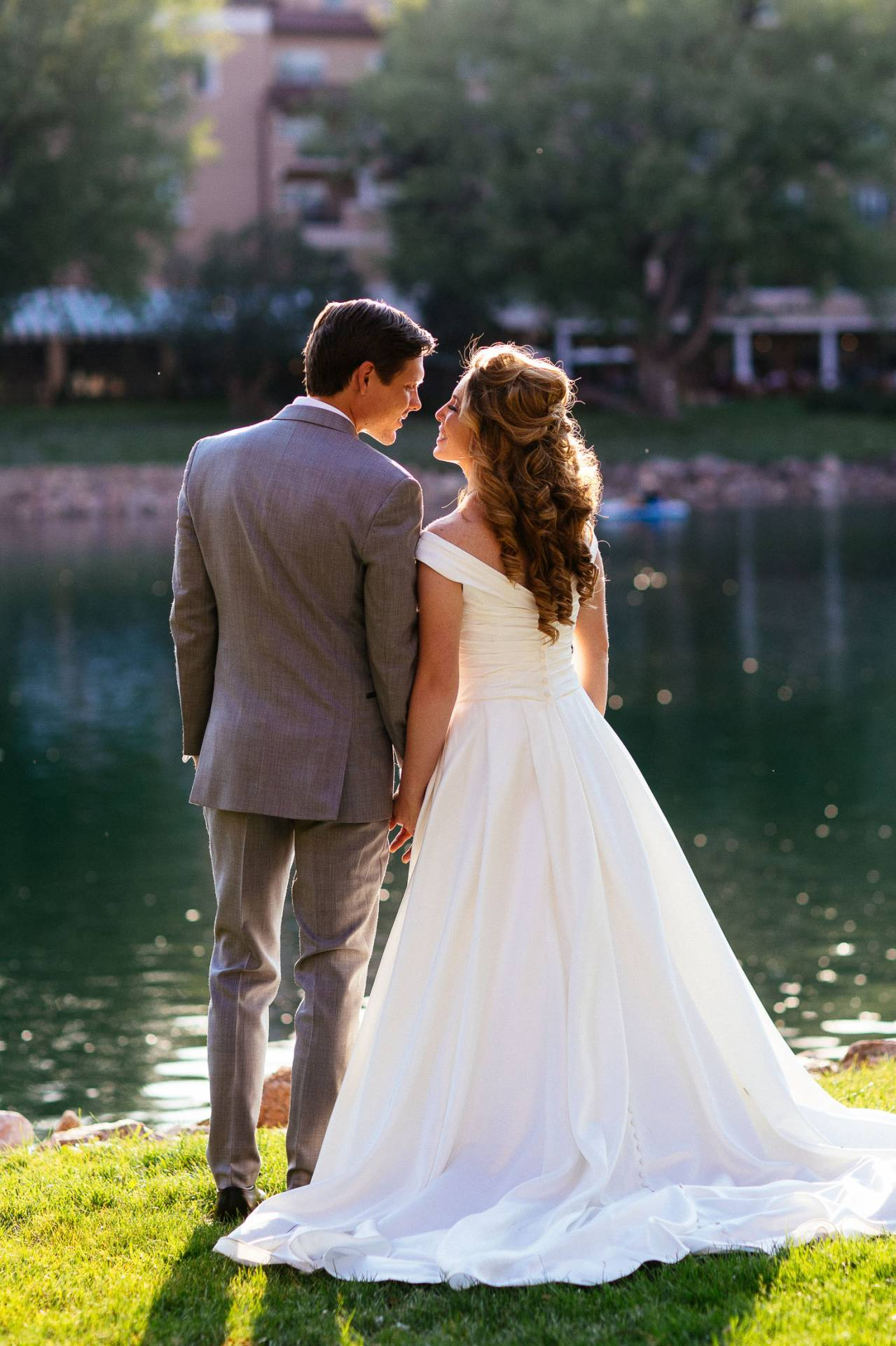 Bride and groom hold hands along the lake at The Broadmoor.