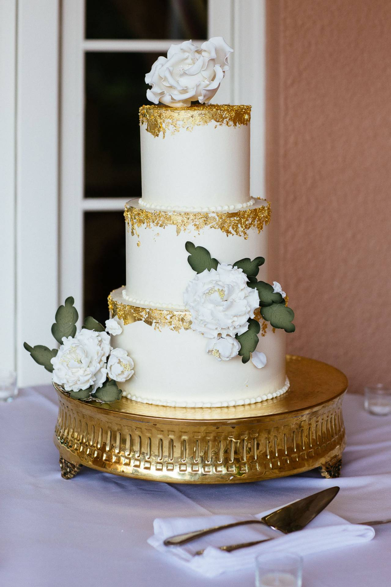 Three-tiered wedding cake with white flowers and gold leaf.