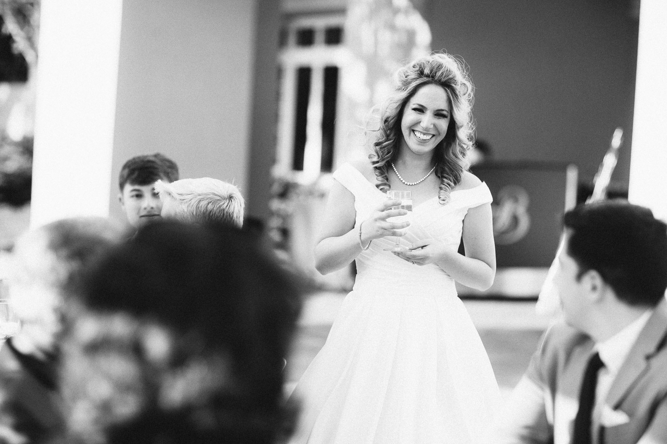 Black and white photo of bride laughing with guests during reception at the South Tower.
