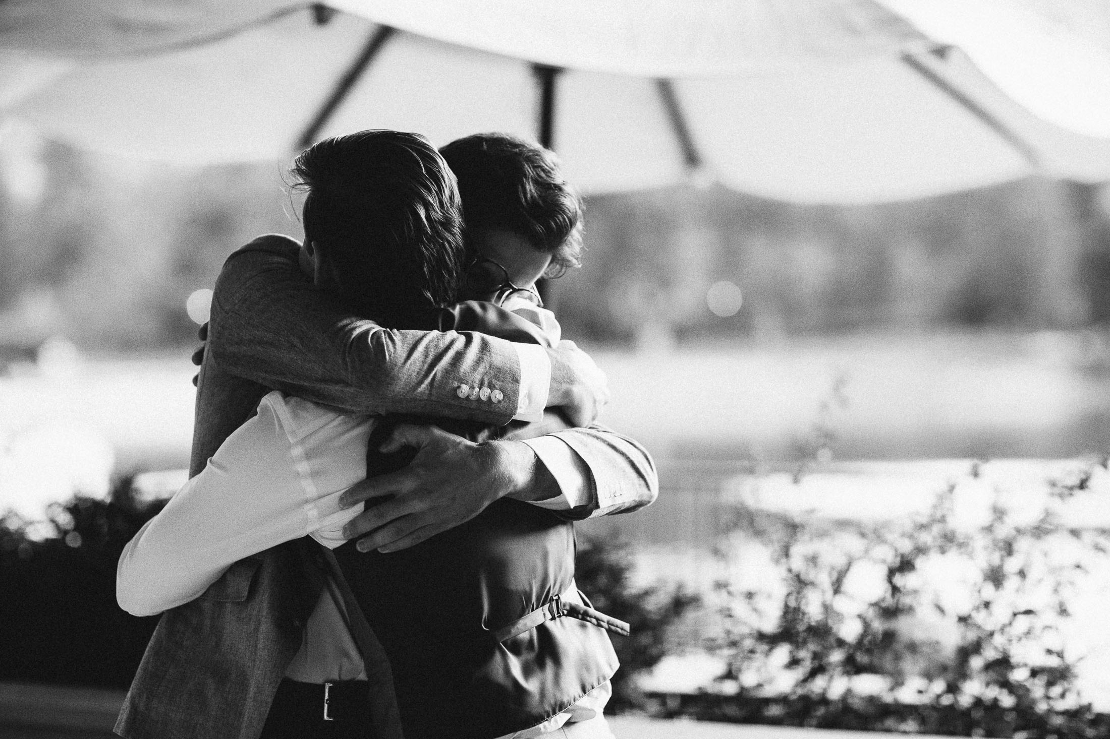 Black and white photo groom hugging best man during wedding reception at The Broadmoor.