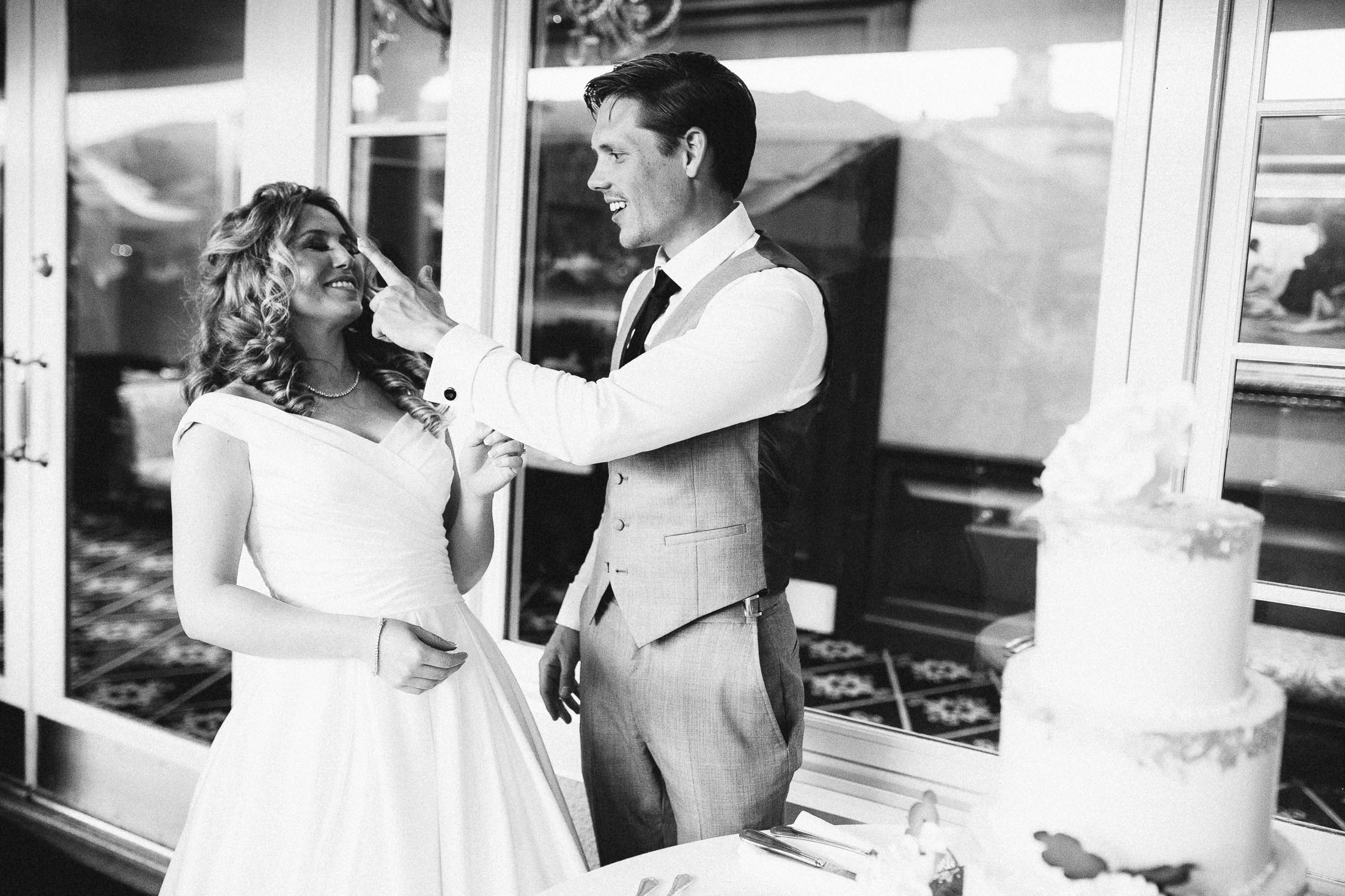Black and white photo of groom with frosting on his finger touching bride.