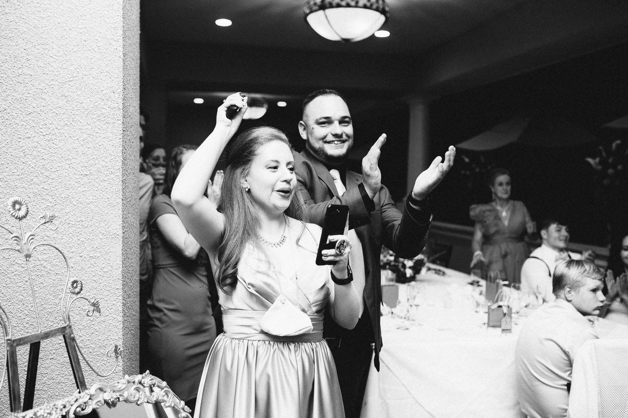 Black and white photo of wedding guests cheering during wedding reception at The Broadmoor.