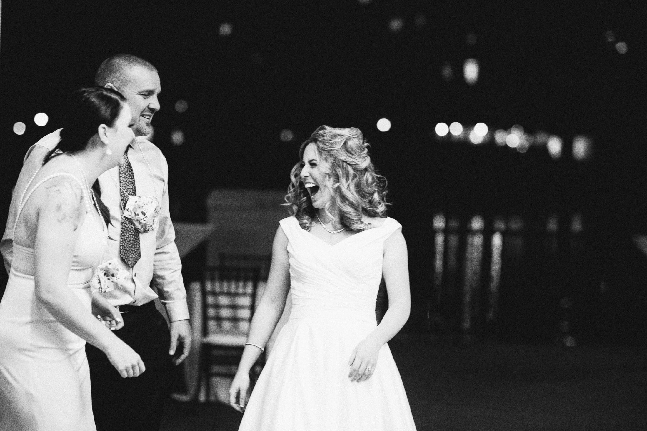 Black and white photo of bride laughing during wedding reception at The Broadmoor.