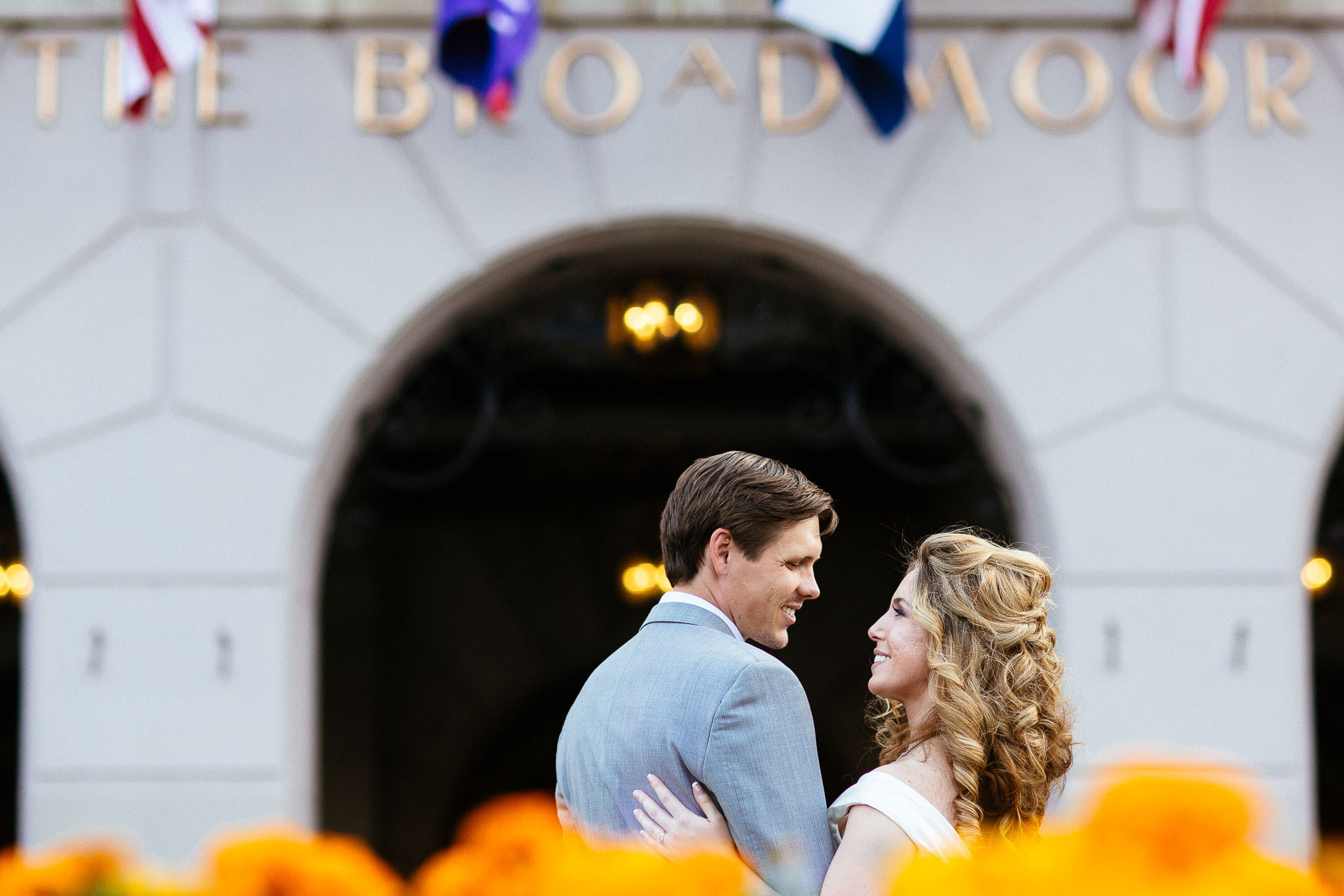 Bride and groom embrace in front of the entrance to The Broadmoor.