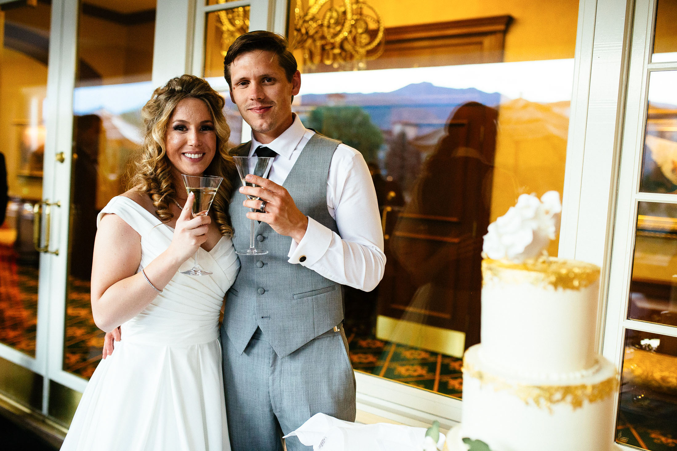 Bride and groom toast each other in front of wedding cake during their wedding reception at The Broadmoor.