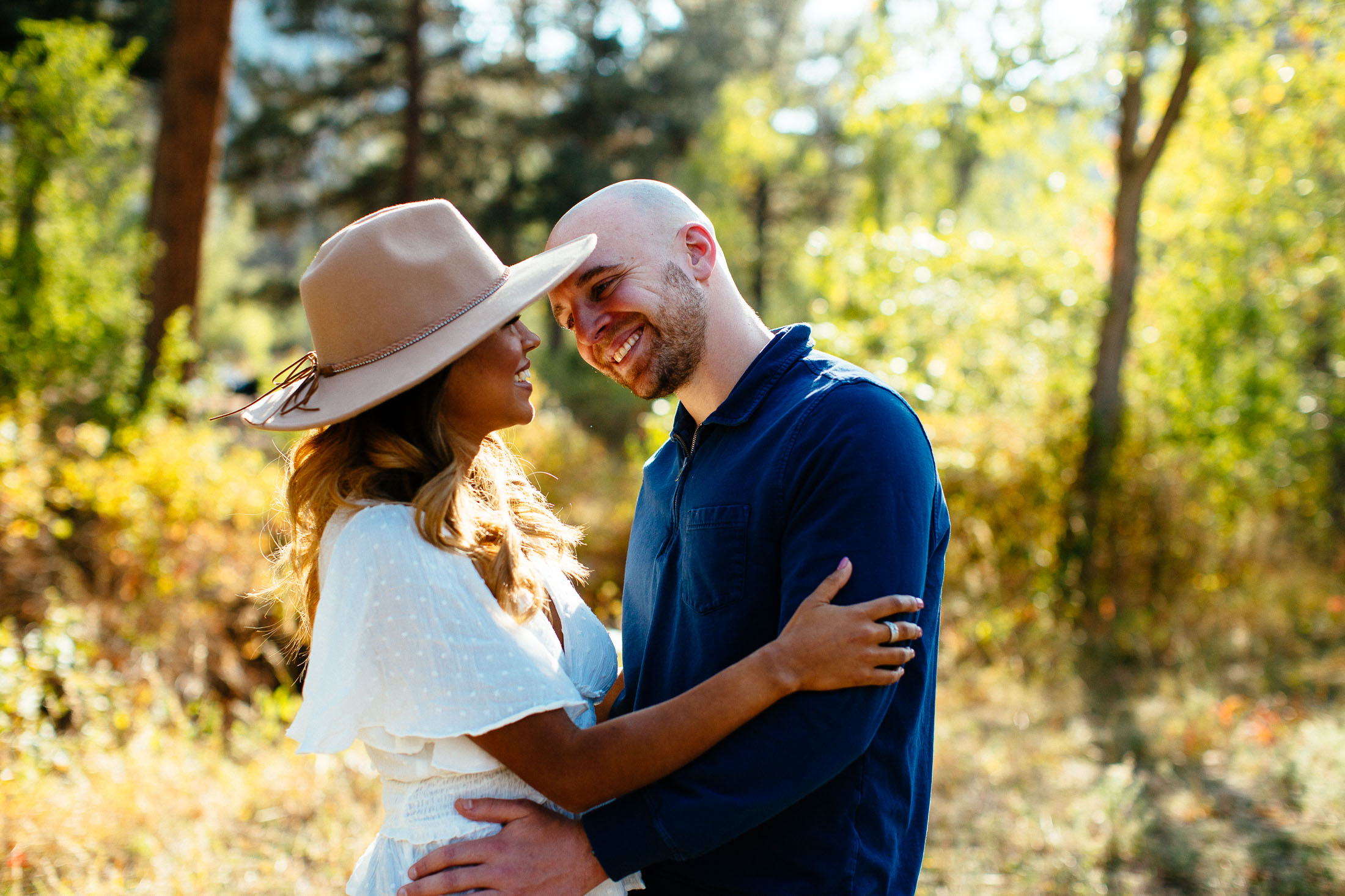 Couple embraces and kisses in a field.