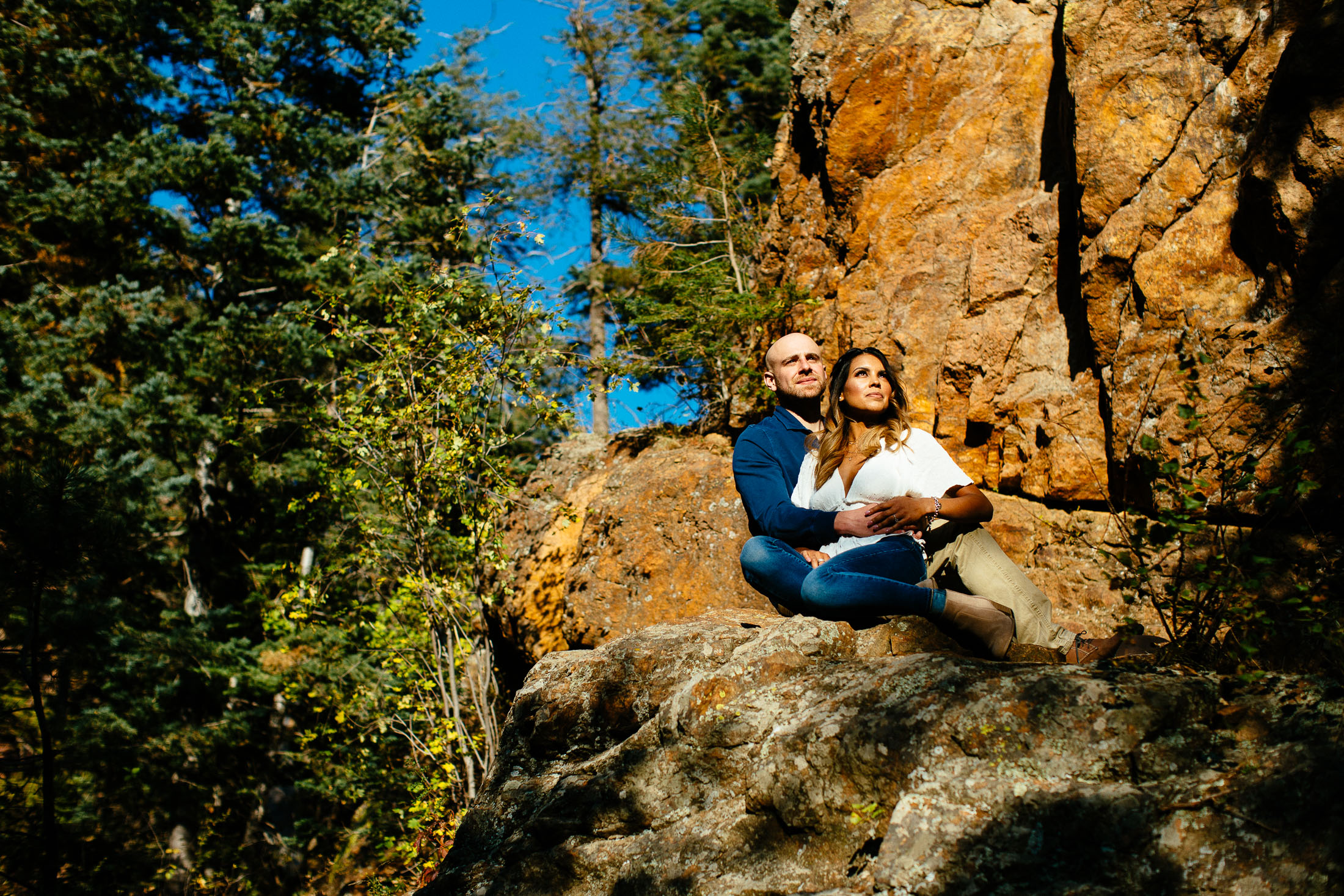 Couple sits on a rock in the sunshine