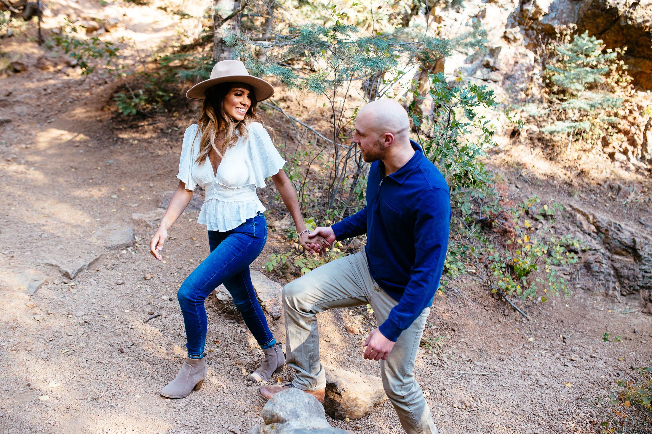 Couple walks on a hiking trail holding hands.