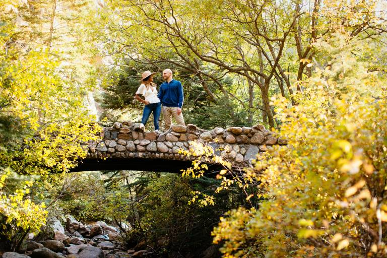 Couples stands on a bridge holding hands in a canon.