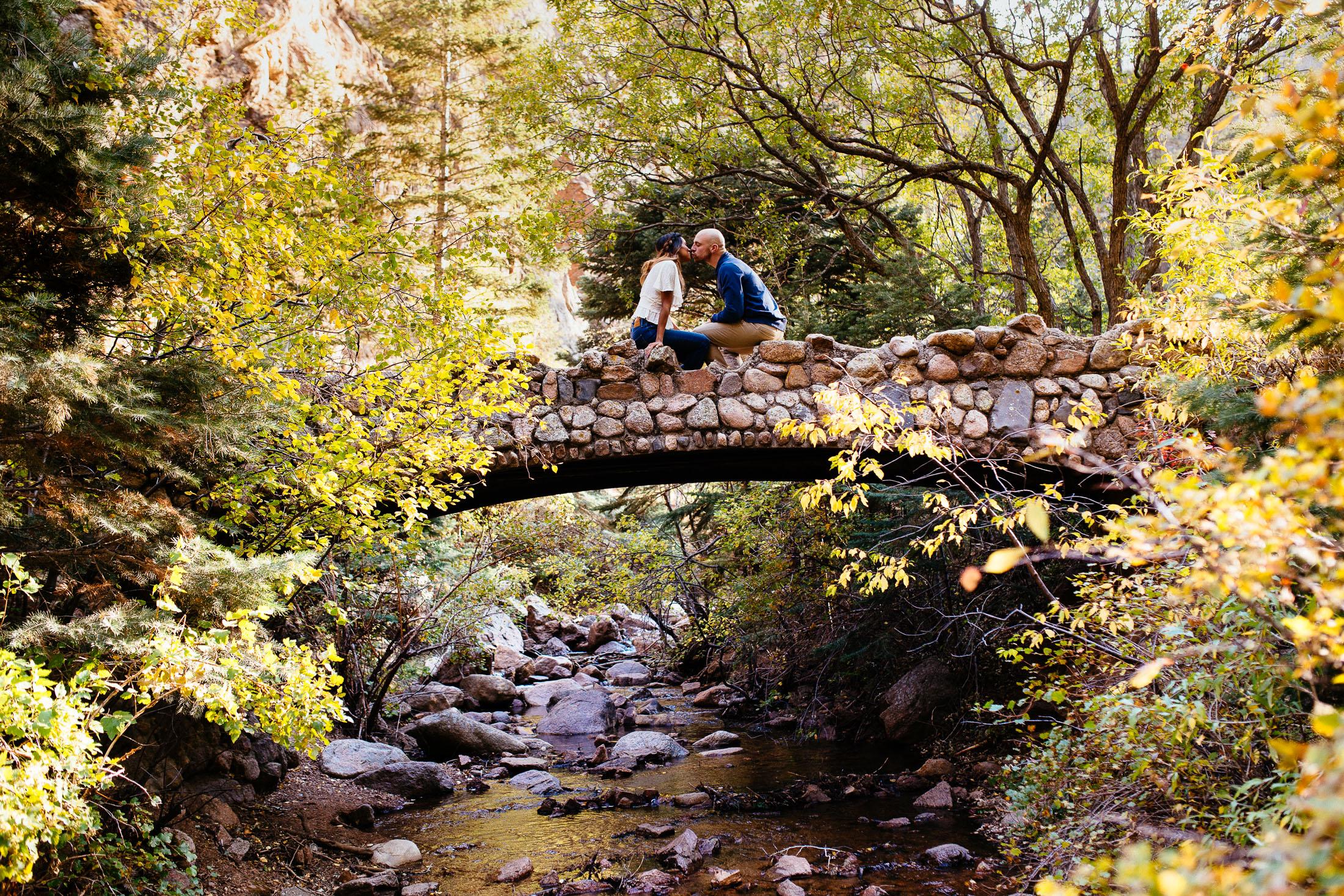 Couple sits on a bridge and kisses.