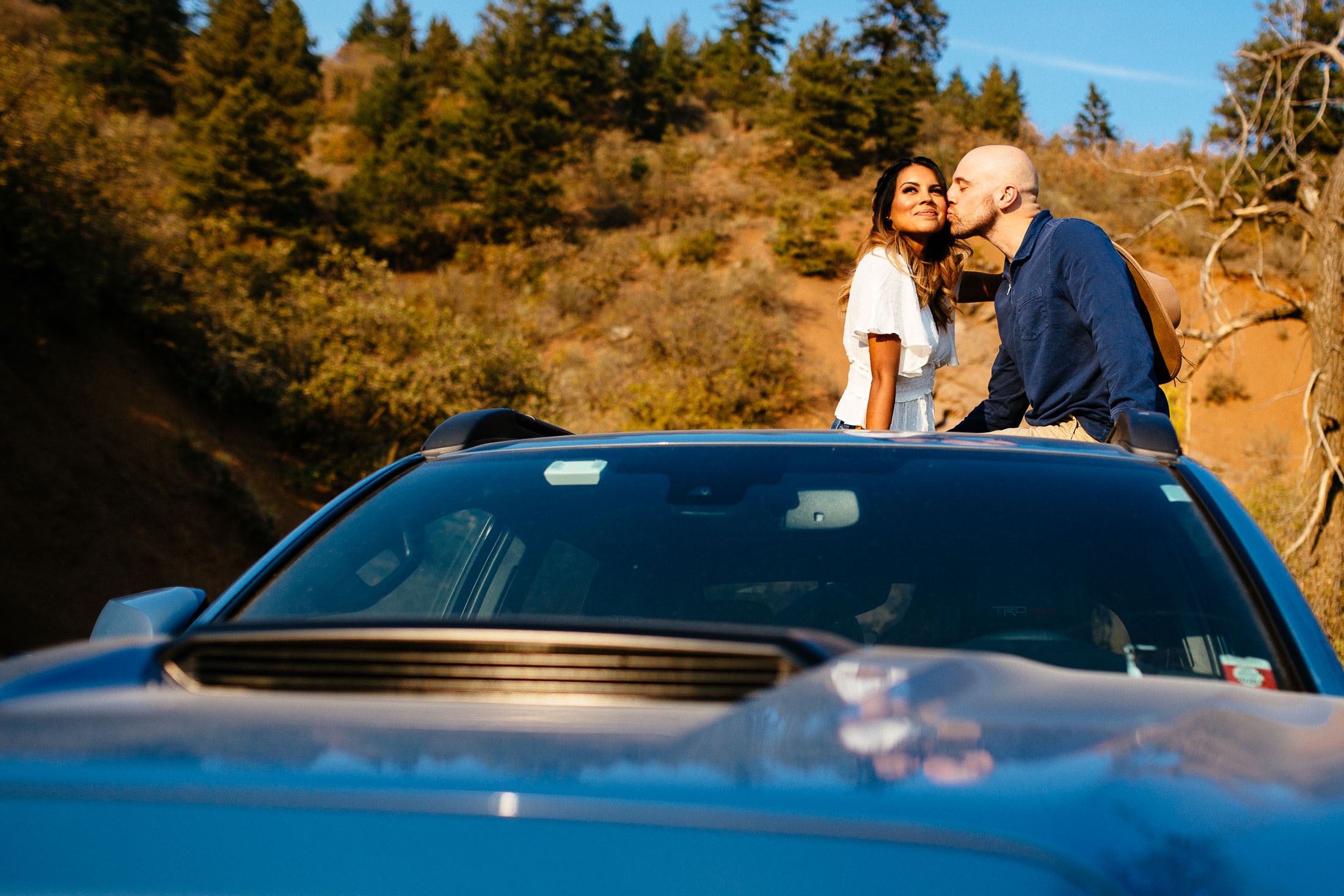 Couple sits on top of a car and kisses.