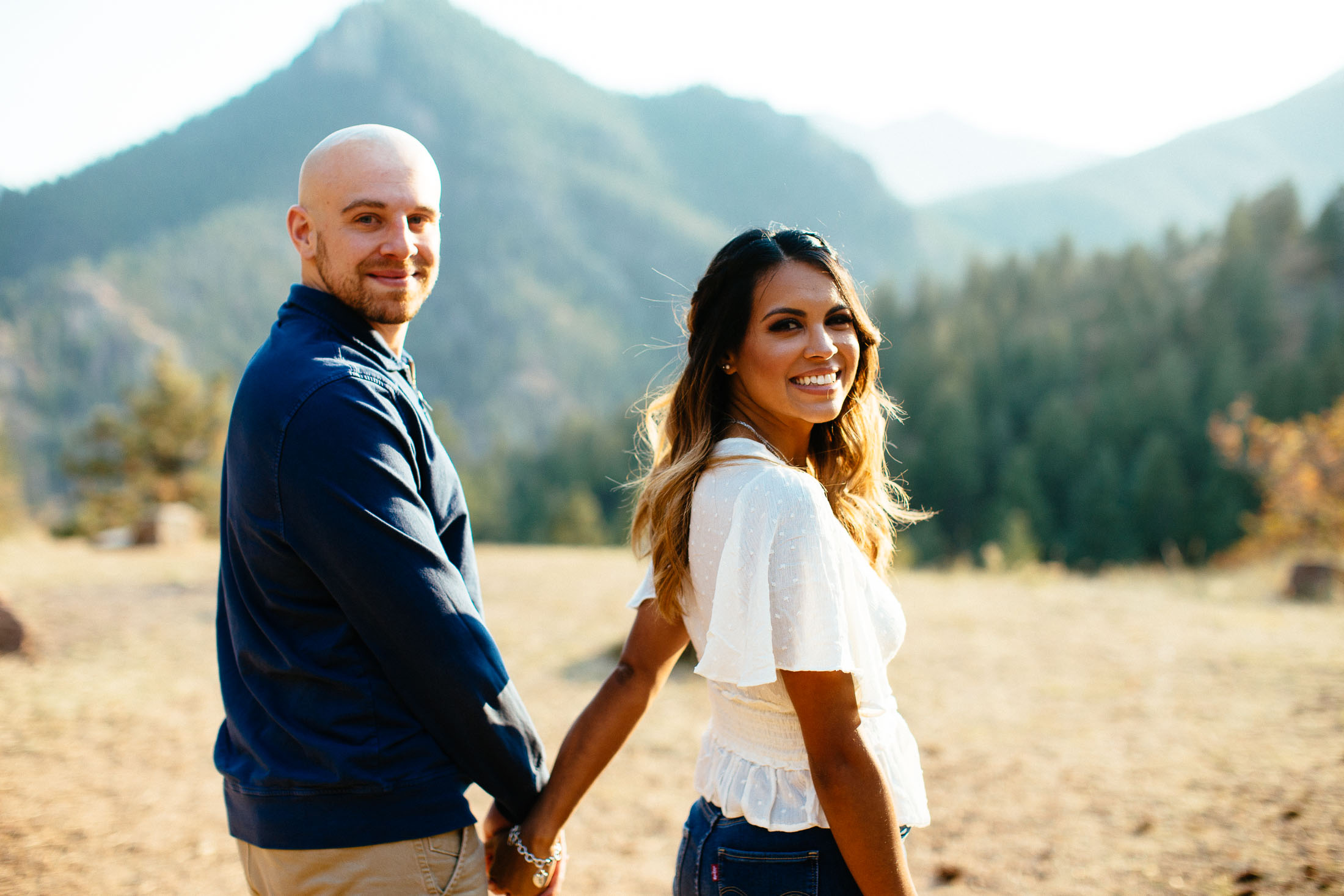 Couple looks back at the camera as they hold hands.