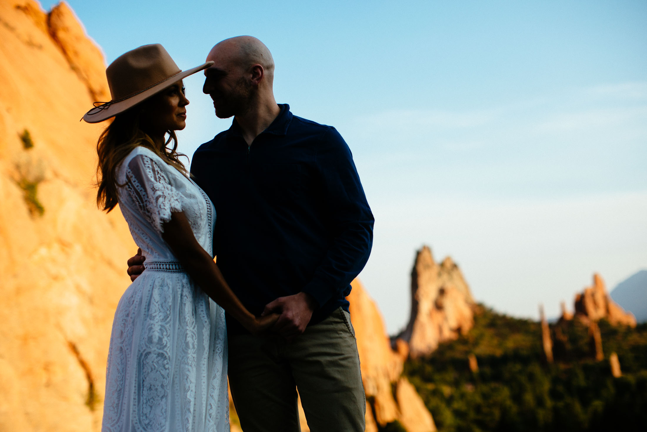 Couple embraces in front of a view of the Garden of the Gods.