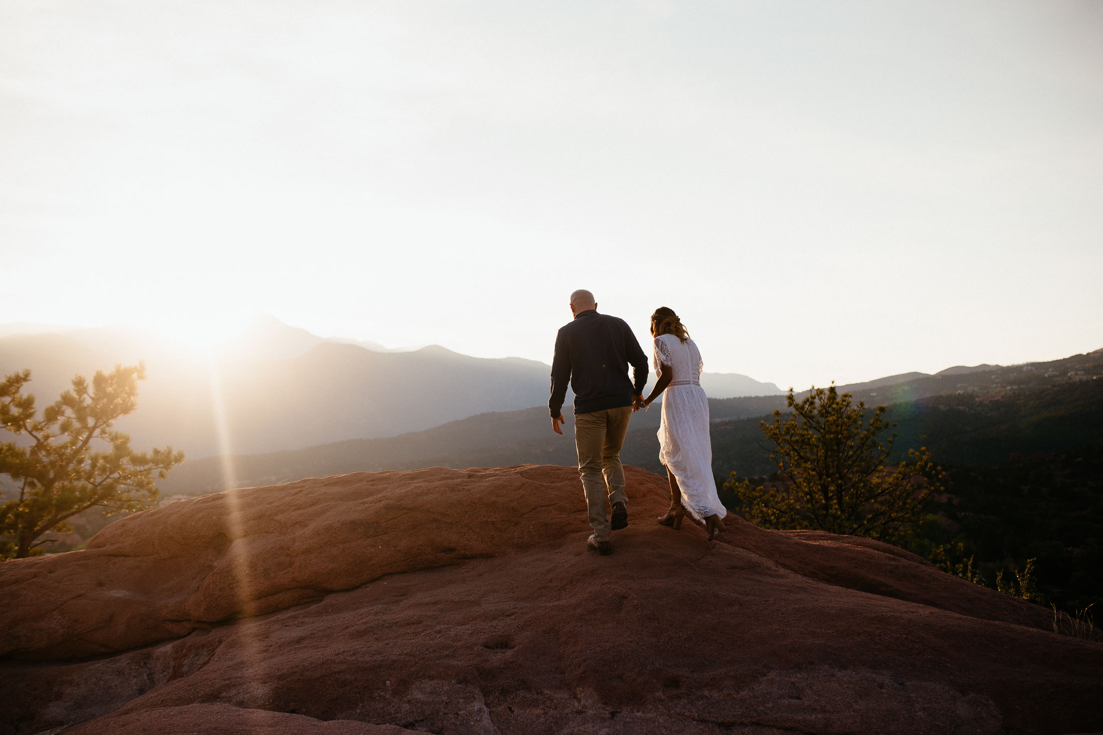 Couple walks on a rock at sunset.