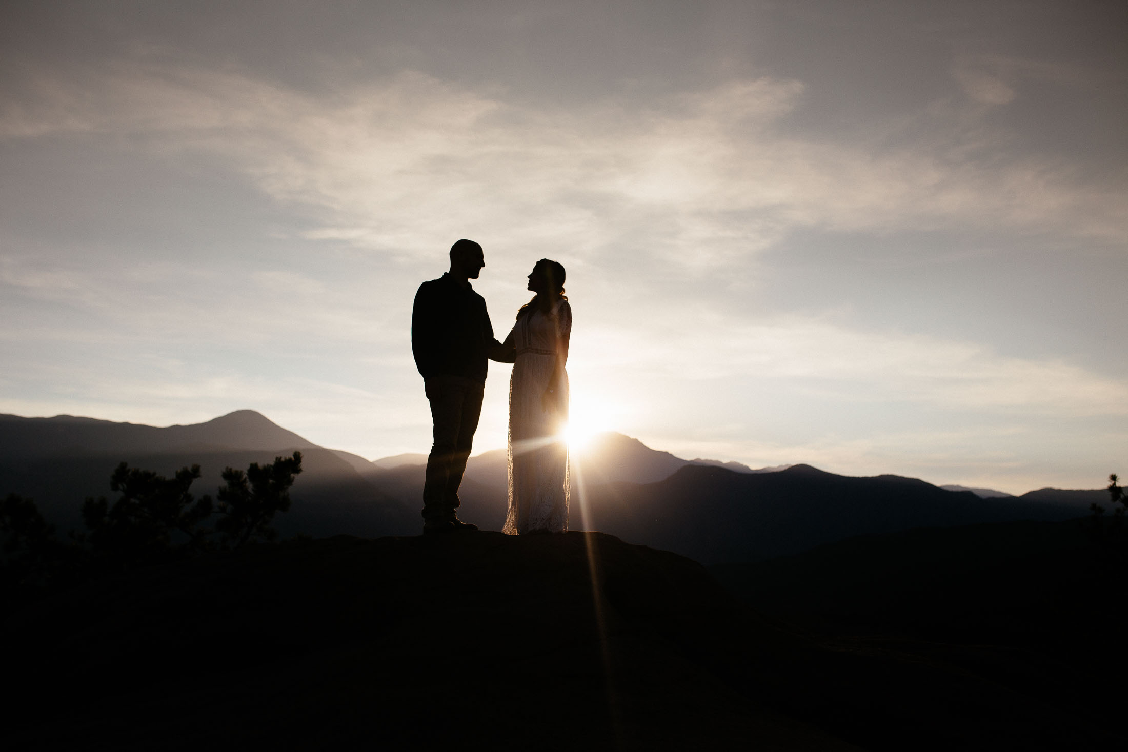 Couple holds hands in front of Pikes Peak at susnset.