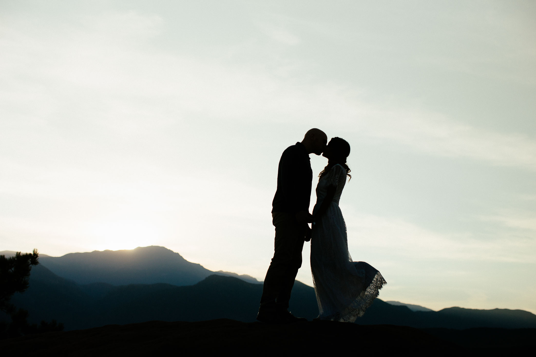 Couple kisses in front of Pikes Peak at sunset.