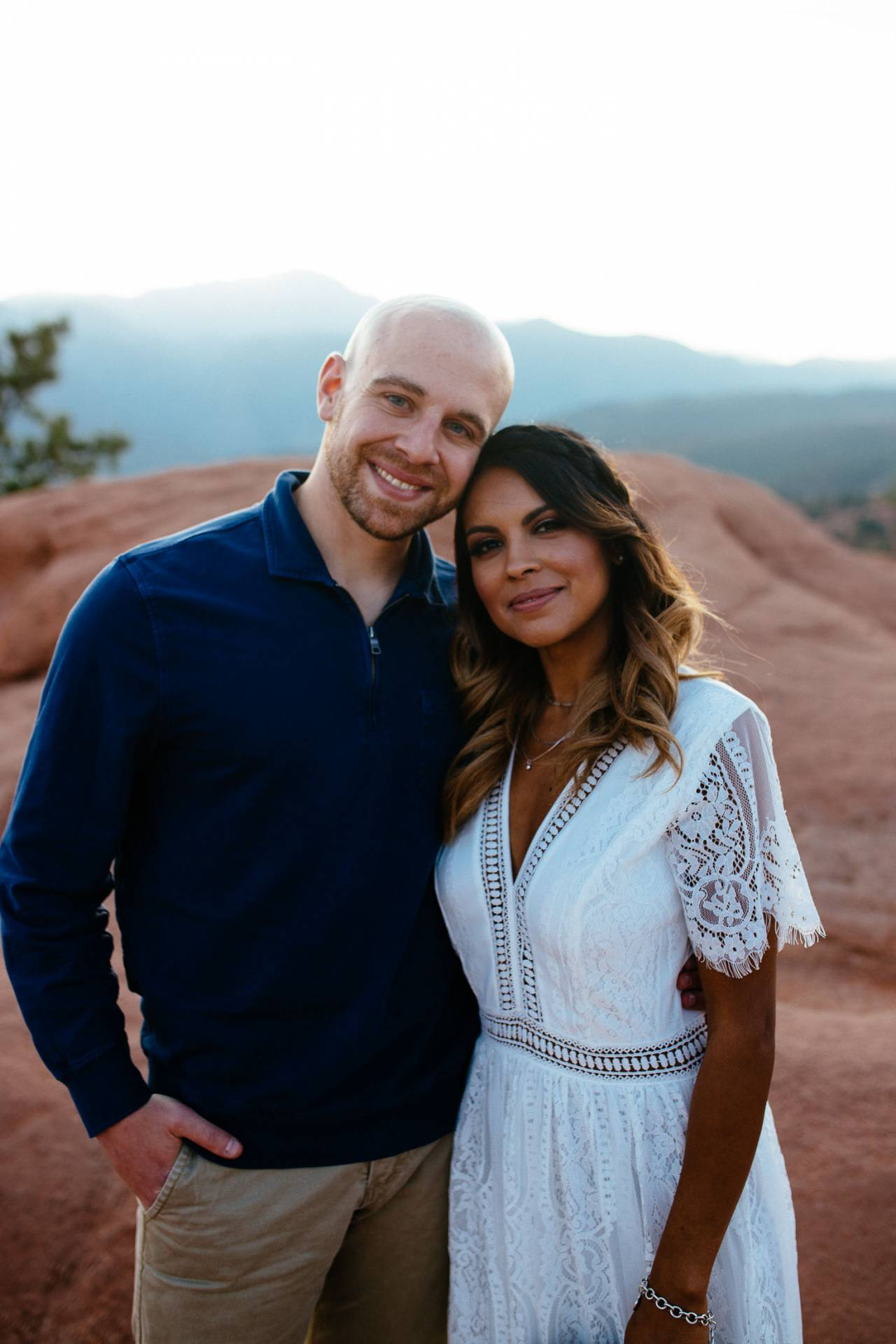 Couple stands in front of Pikes Peak at sunset.