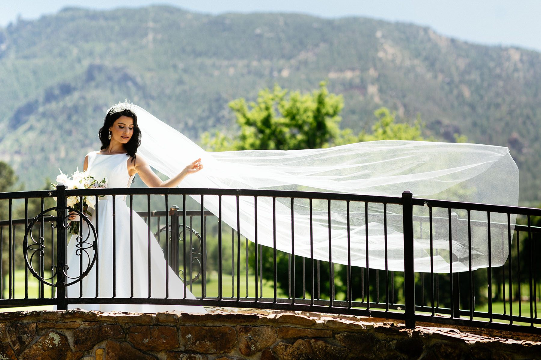 Bride standing on bridge with veil blowing in the wind.